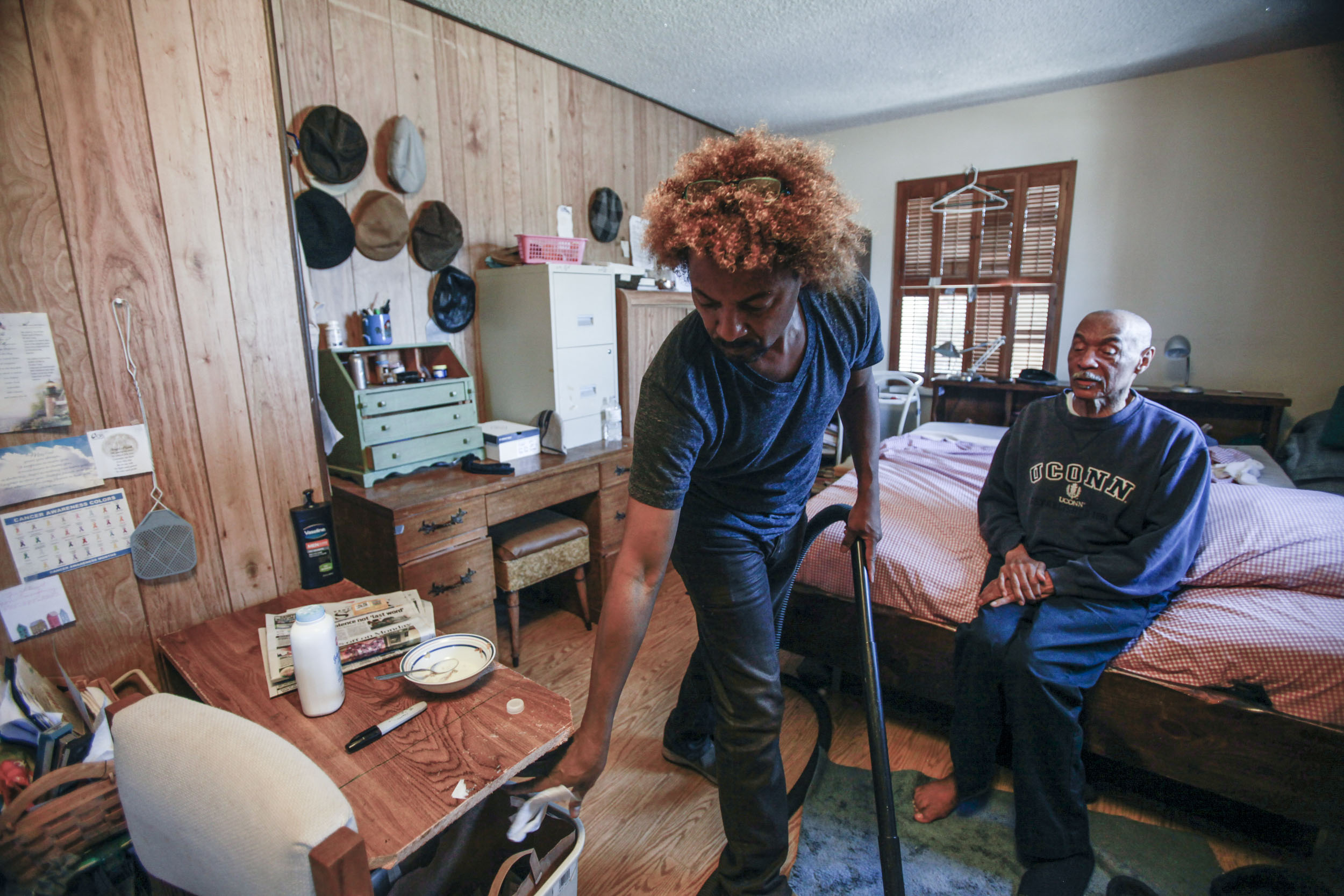 "Mitchell (left) cleans his parents room while his father, Anglee Mitchell (right) closes his eyes. ""You just have to go along with what they say when it comes to dementia,"" Mitchell's mother, Ella Mitchell says. This was photographed in Oxnard, Calif. on Oct. 5, 2015."