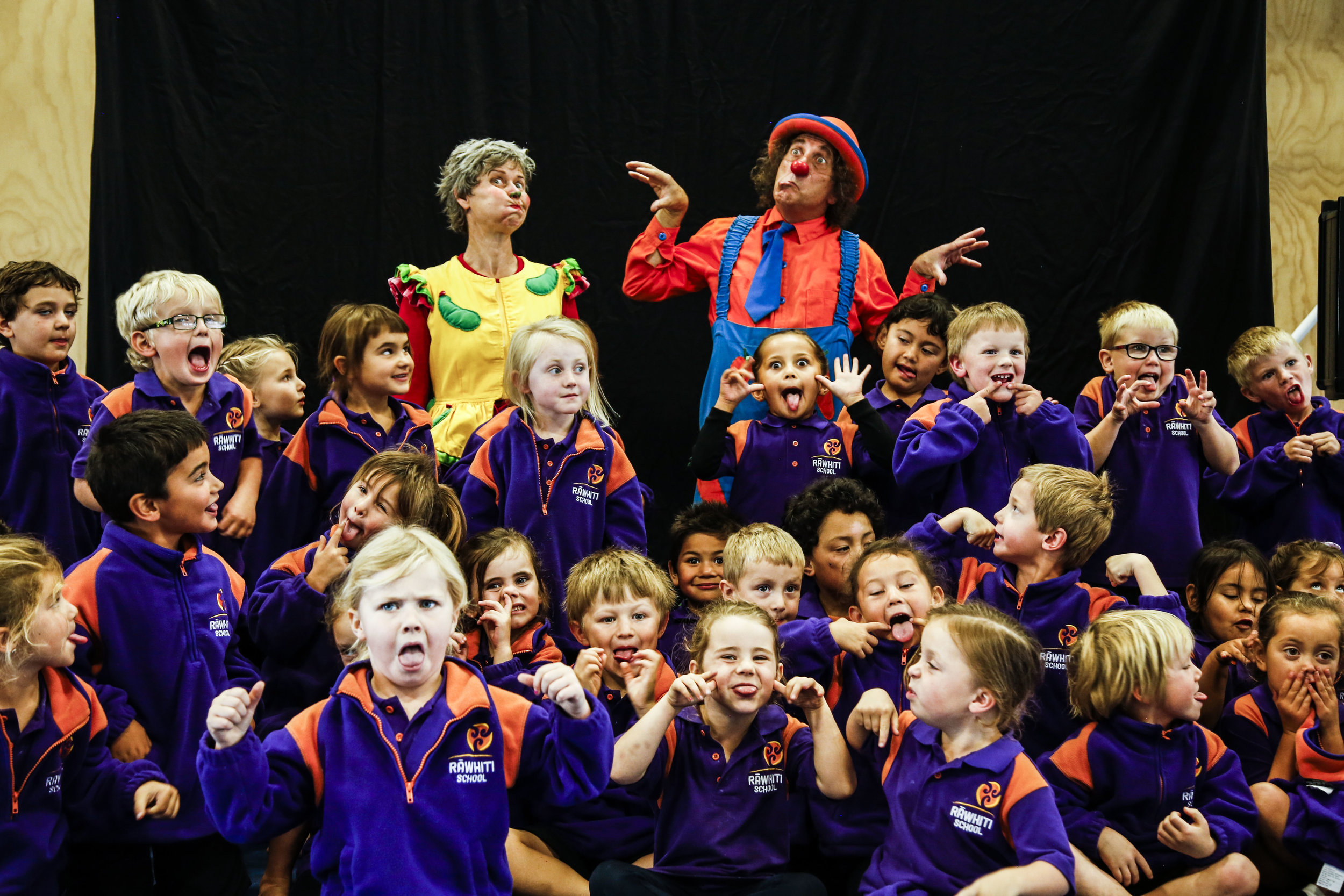"Wingfield (left) and Carrow (right) pose for pictures with the students after their performance on May 6, 2016 at Rawhiti School in Christchurch, NZ. ""I love seeing the joy in children when we perform,"" says Wingfield."