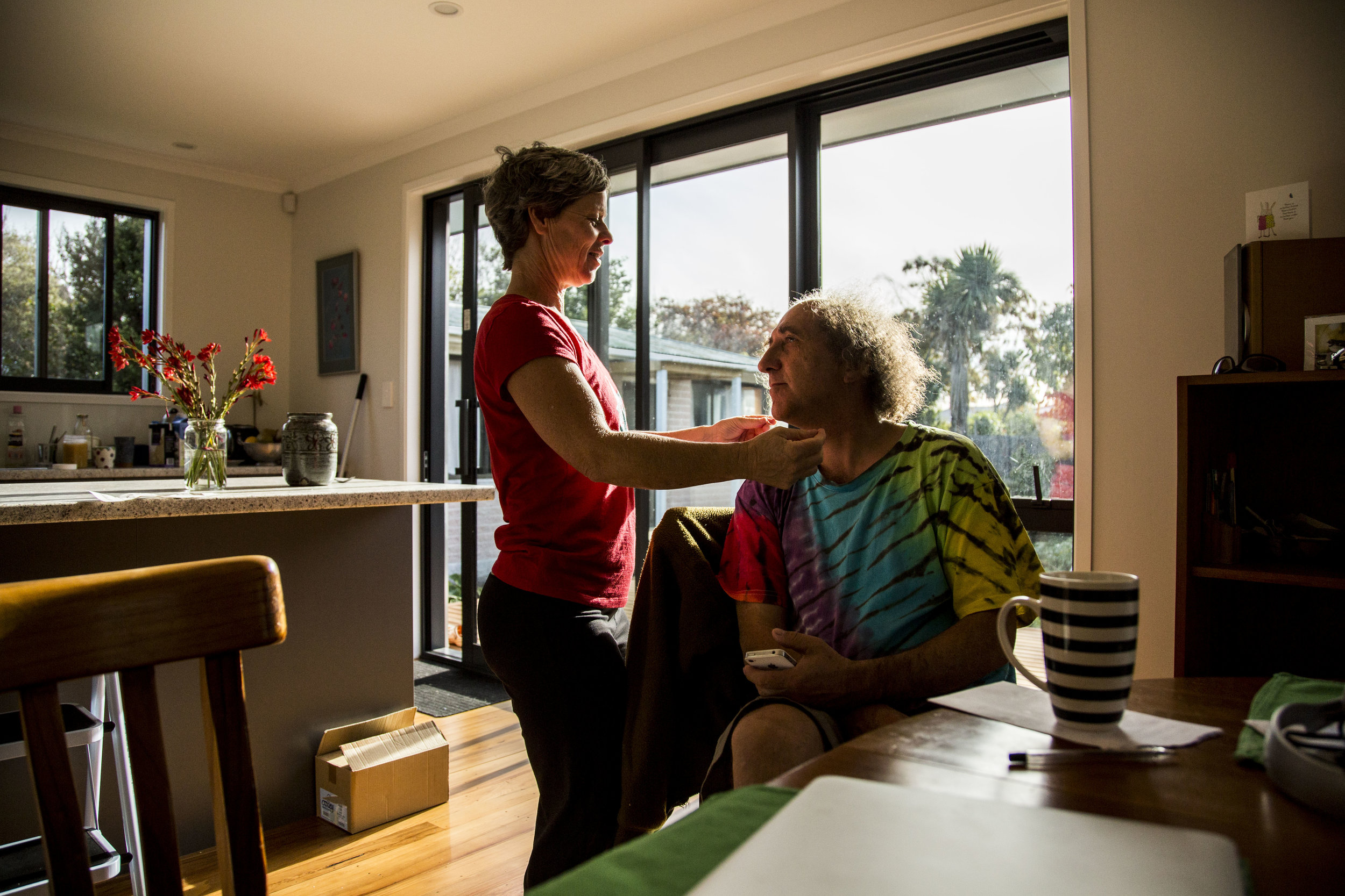 Wingfield (left) and Carrow (right) embrace in their Christchurch, NZ home on May 3, 2016. In addition to losing their circus school, their home was also destroyed in the aftermath of the earthquake. They've just recently finished rebuilding their home.