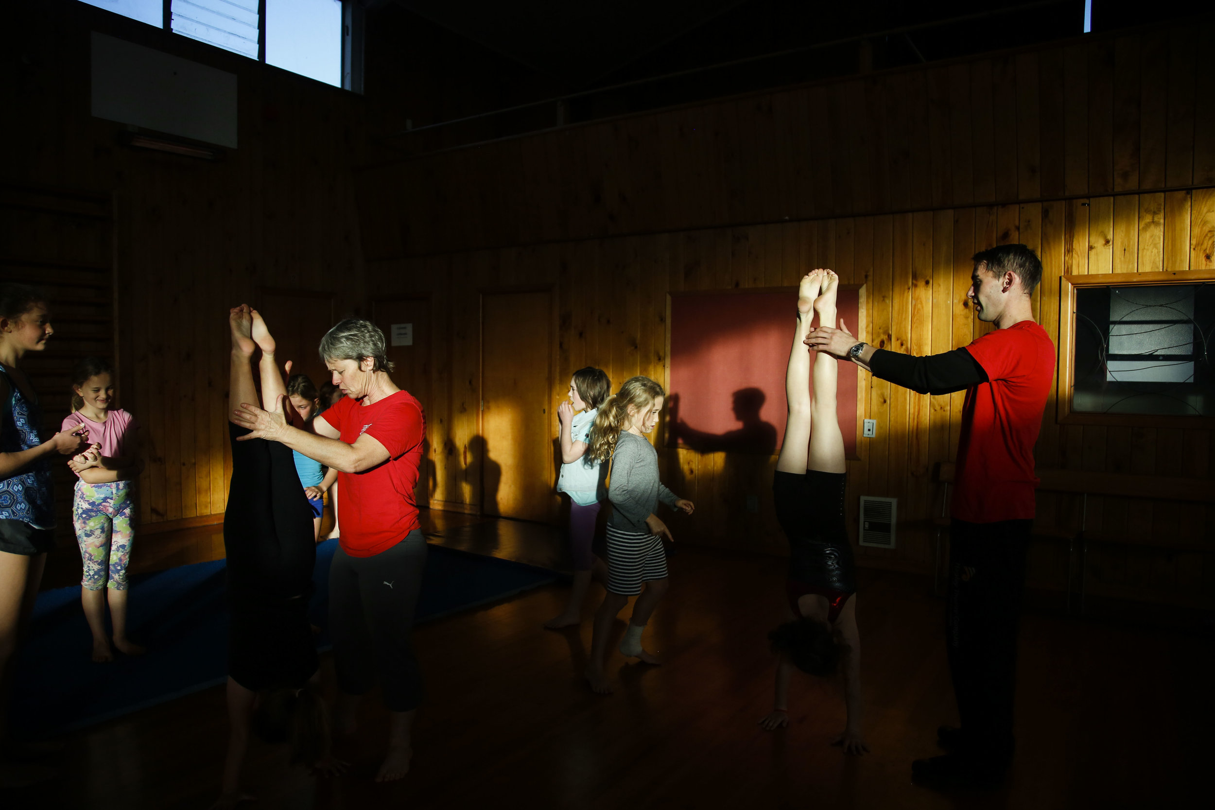 "Wingfield (left) helps a student with her handstands during a class at the Christchurch Circus Centre in Christchurch, NZ on May 10, 2016. Wingfield and Carrow lost their original circus school to the 2011 Christchurch Earthquake. ""We lost our circus school and started doing community circus workshops in town. But then that building had to get demolitioned as well. So we had to find a new venue. Luckily enough, Chris is really good at hunting for stuff."""