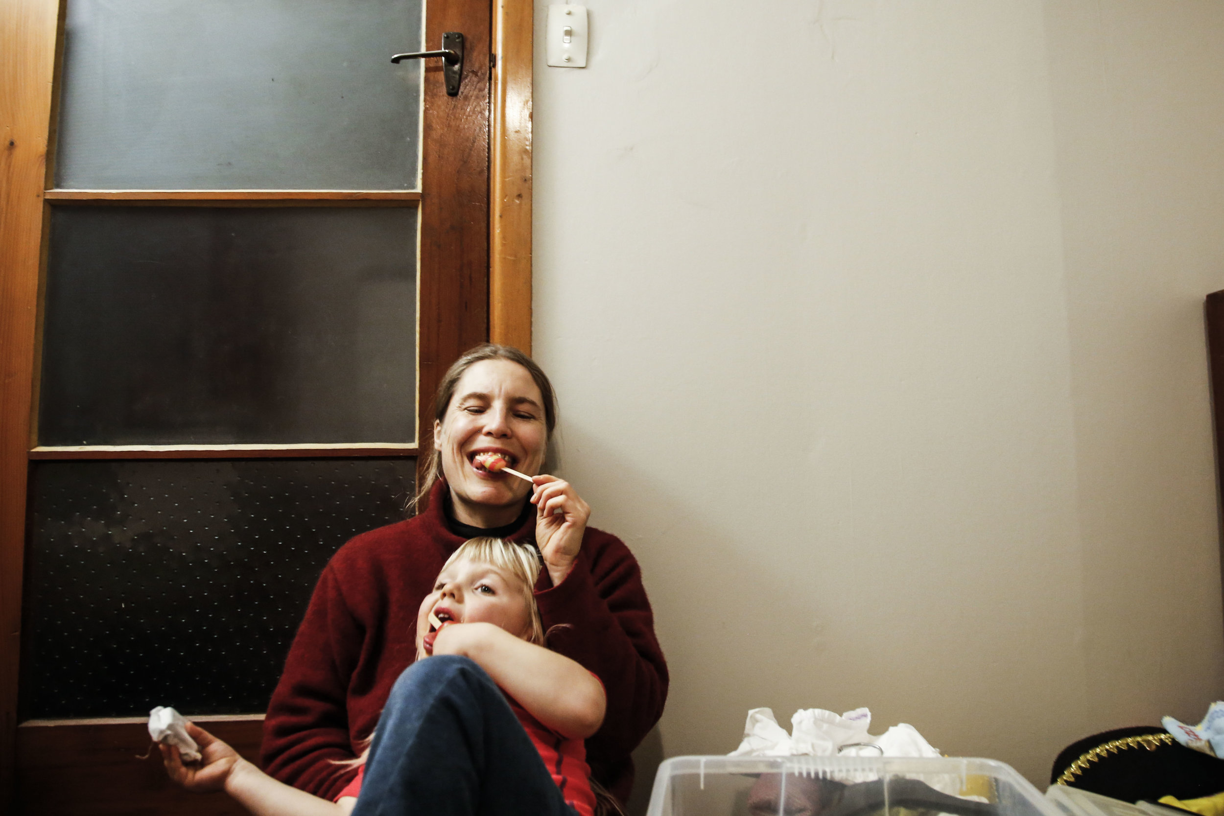 Olivia Ricken (center) and Auriel Ricken (center-front) eat popsicles together in their Christchurch, NZ home on May 26, 2016. Olivia Ricken, a clown and circus performer, was also deeply affected by the 2011 Christchurch Earthquake. She was forced to move out of several homes with her five year old son, Auriel, in addition to losing her circus school building at the Christchurch Polytechnic Institute of Technology.