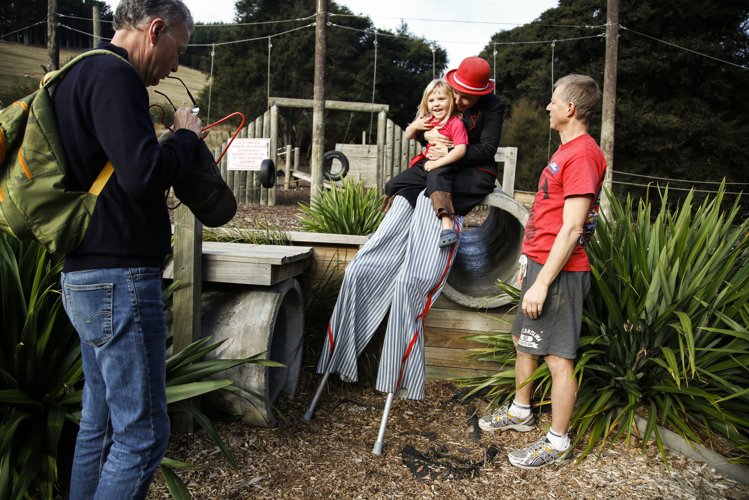 "Neil Wooten (left), Ricken's boyfriend, wipes his glasses as Auriel and Olivia Ricken (center) laugh together at Orton Bradley Park in Charteris Bay, NZ on May 14, 2016. ""My son is so proud of his mum. He goes through the kitchen and tries to balance everything on his nose because he's seen me do it. It's very sweet,"" says Ricken. Wooten and Ricken were also accompanied by Auriel's father, Andre Heppelthwaite (right). Ricken and Heppelthwaithe try to maintain a good relationship for Auriel."