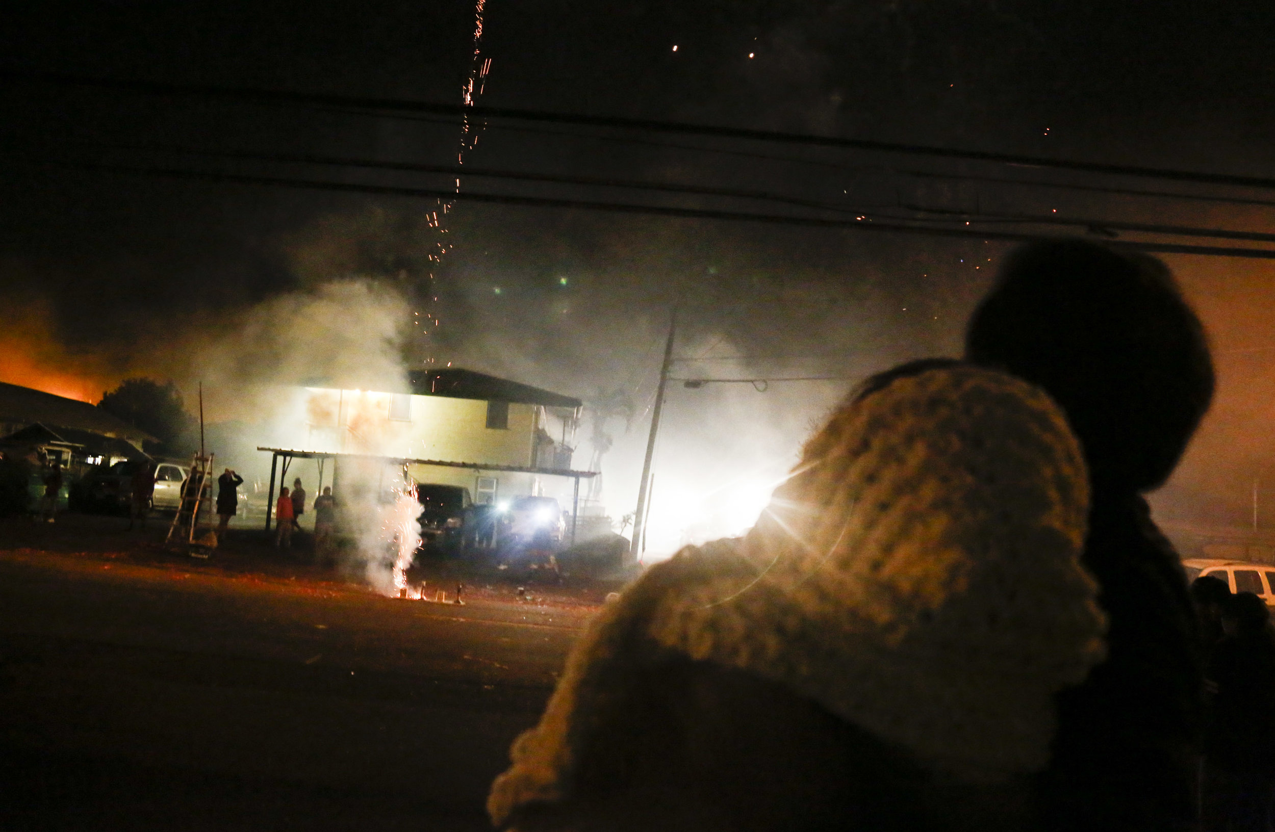 My mother (left), watches fireworks being lit by our neighbors on our street with my father, Daniel Hobro (right), on New Year's Eve. Even though fireworks are now illegal in Hawai'i, this doesn't stop locals at all. Wahiawa becomes a clouded city full of smoke during this holiday.