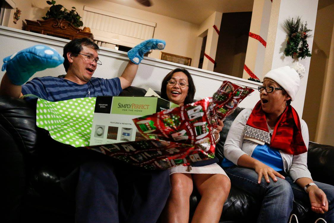 (From left to right) My father, mother and godmom, Lilian Nachman, excitedly open their Christmas gifts at our hanai family's house. My Tita Lilian is my mother's best friend and helped take care of us when we were babies.