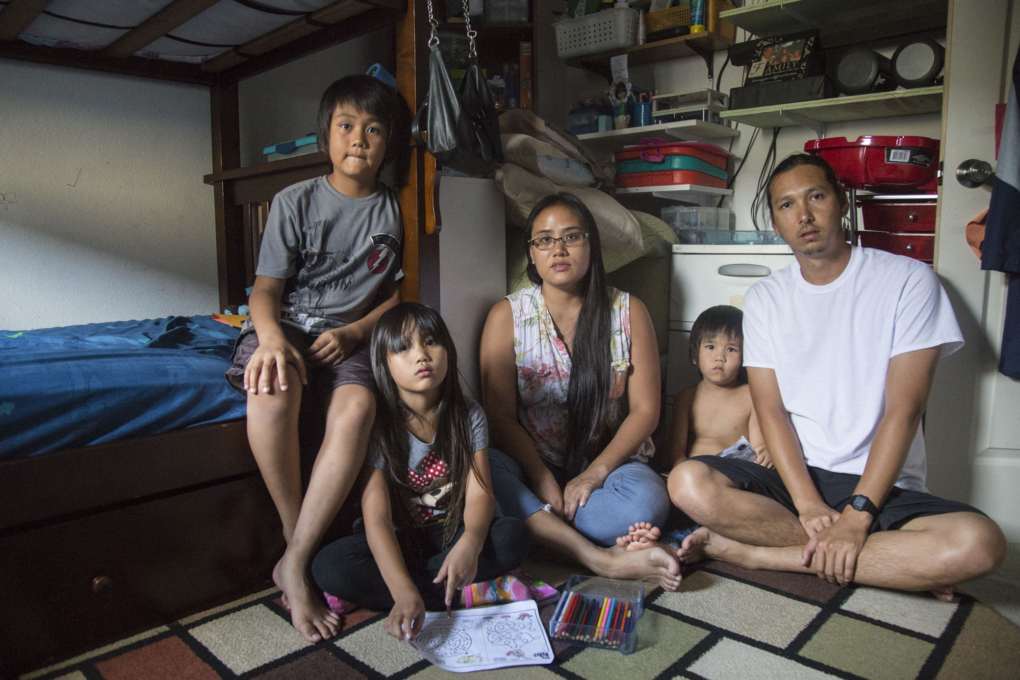 "Tyler Okamura Tagupa and Ashley Lata pose for a portrait with their children, Rev, Erin, and Levi, in the small bedroom they all share. They moved to Lataʻs family home in Ewa Beach, Hawaiʻi, earlier this year in March to save money. Their three children share the bunkbed while the couple sleep together on a floor mattress. ""Living with 14 people was a culture shock at first. This is Ashleyʻs family home, but I only grew up with my mom as an only child. We live with her mom and dad, two sisters, their kids, and our kids. Her grandma used to be here too. Itʻs a little hard because weʻre a big family of five, but weʻre saving two or three grand every month in savings to put down for our own place. If we stay home, we can find somewhere we like and not get stuck in a contract. Itʻs possible to get ahead in Hawaiʻi, but the cost of living doesnʻt help. Right now, my annual salary is around a low $61-62,000 and I have a family of five,"" Tagupa says. An annual income of $96,000 is considered low income in Hawai'i for a family of four. The Tagupa family is planning on moving into their own home later this year."
