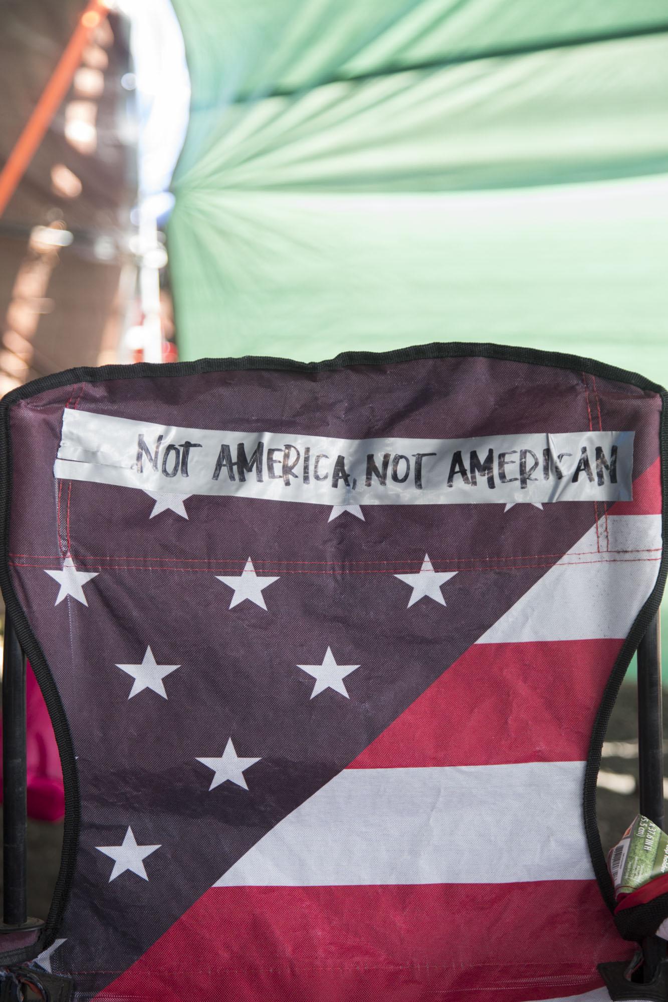 "A chair reading ""Not America, not American"" sits in Puʻuhonua o Puʻuhuluhulu, a refuge for all those protecting Maunakea."