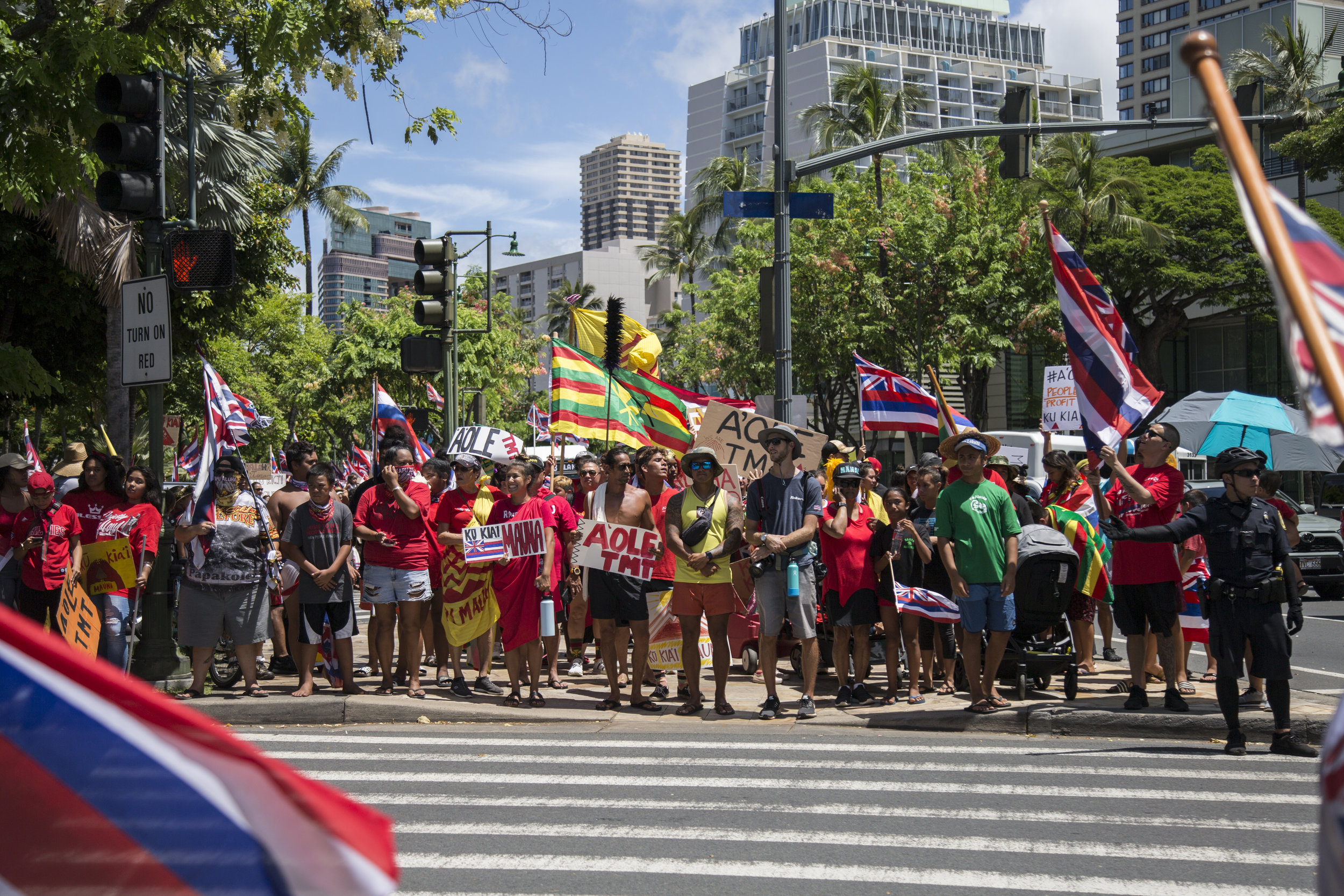 Kiaʻi wait at a crosswalk during Waikiki for Maunakea on July 21, 2019. On this day, thousands of people marched along Kalakaua Avenue in Waikiki in support of Maunakea.