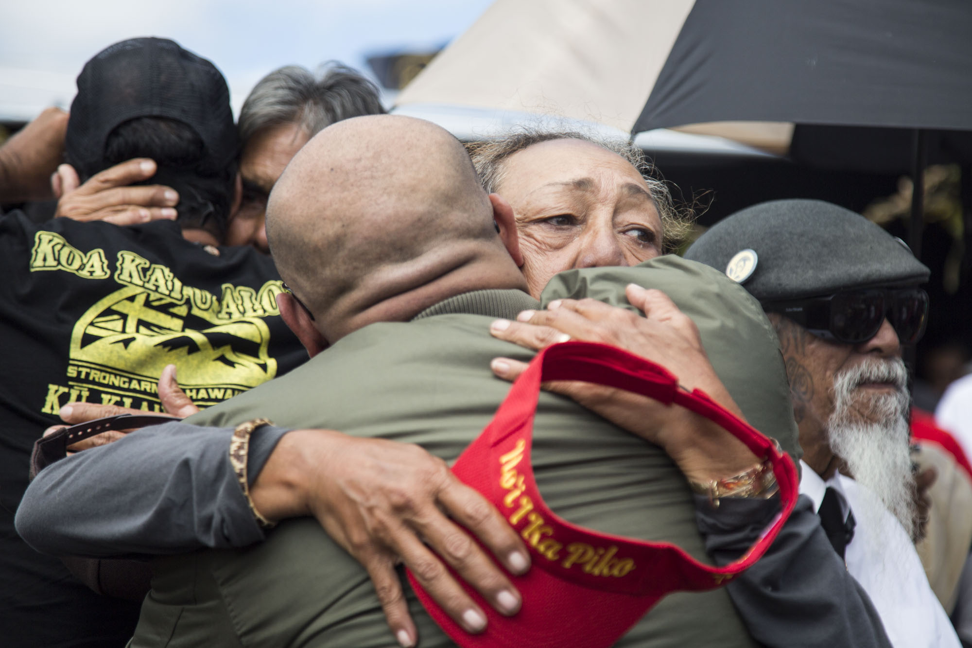 """Nohea Kalima, one of the 38 kūpuna arrested for protecting Maunakea, hugs a family member of George Helm after giving hoʻokupu. Helm was a beloved musician and Native Hawaiian activist who occupied Kahoʻolawe alongside eight other activists in 1976. Together, Walter Ritte, Emmett Aluli, Ellen Miles, Karla Villalba, Steve Morse, Kimo Aluli, Gail Kawaipuna Prejean Ian Lind, and George Helm were known as the """"Kahoʻolawe Nine"""". They successfully stood against the militaryʻs use of the island as a bombing range. Both Helm and activist Kimo Mitchell disappeared in 1977 while they were out at sea. Today, the bombing has ceased and the island is in the process of restoration."""