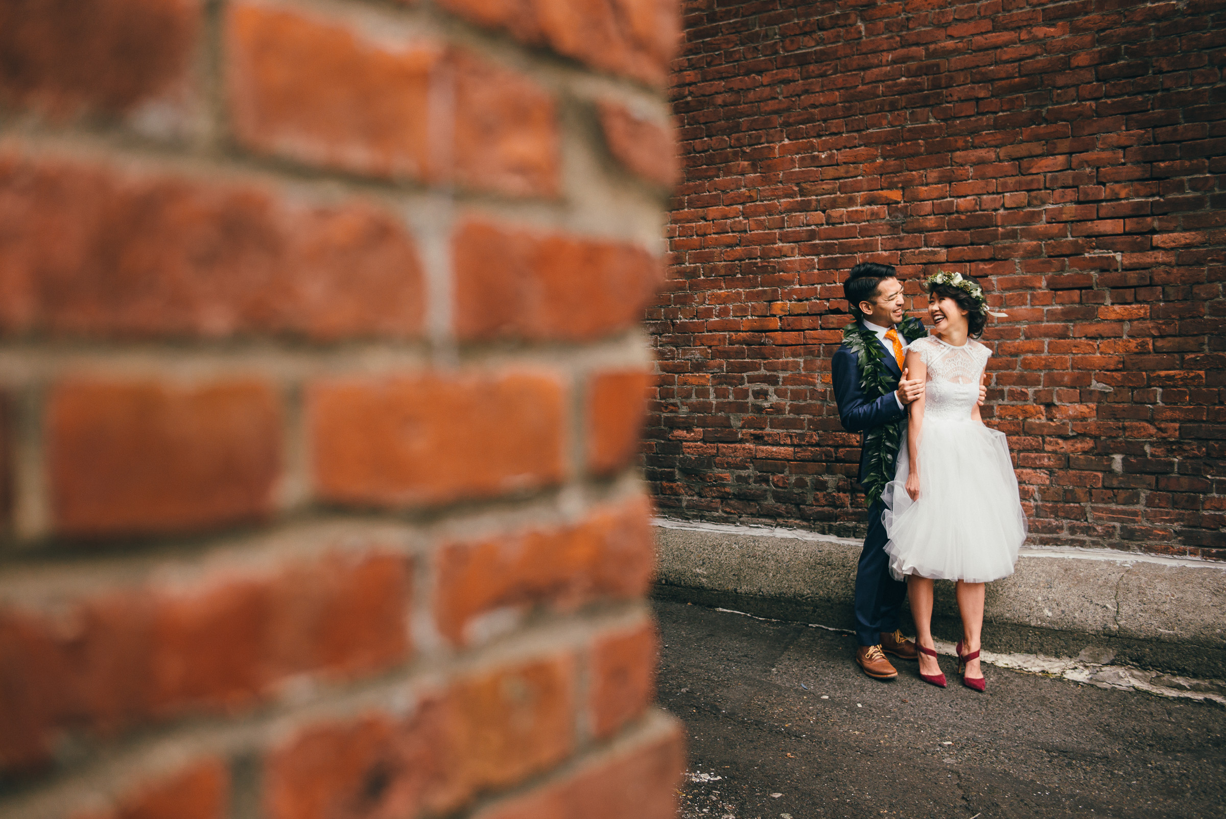 Asian Wedding Couple Portrait Against Brick Building in Pioneer Square, Seattle.