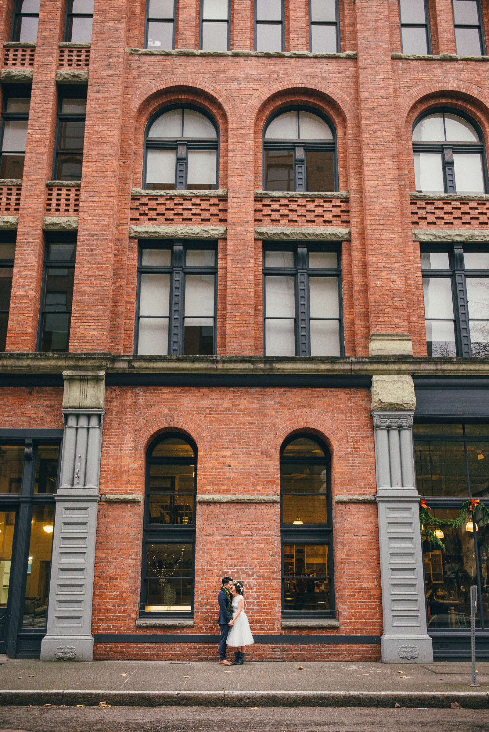 Bride and Groom Portrait Against Brick Building on their Wedding Day in Seattle