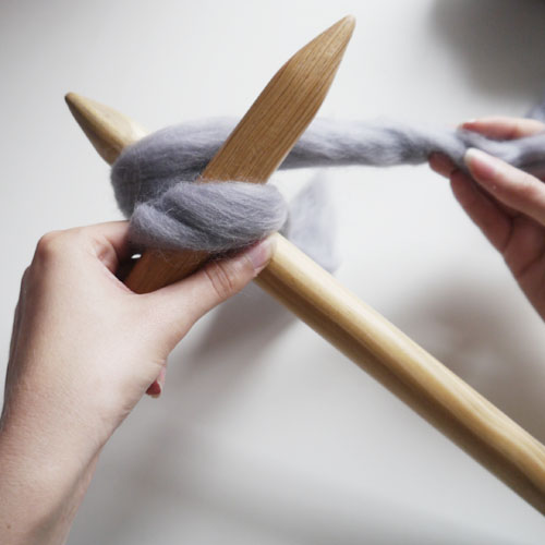 Step 5 - Wrap your yarn (attached to the ball of wool not your small tail) anti-clockwise around the head of your right needle...