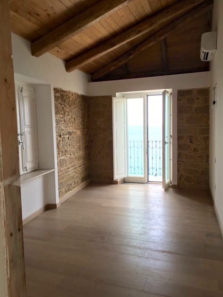 Dependance: The second bedroom with small balcony facing the sea and restored stone wall