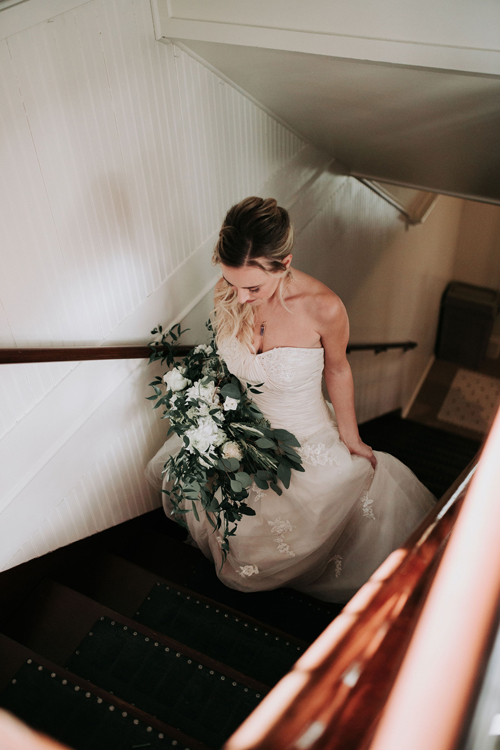 Bride climbing stairs with bouquet