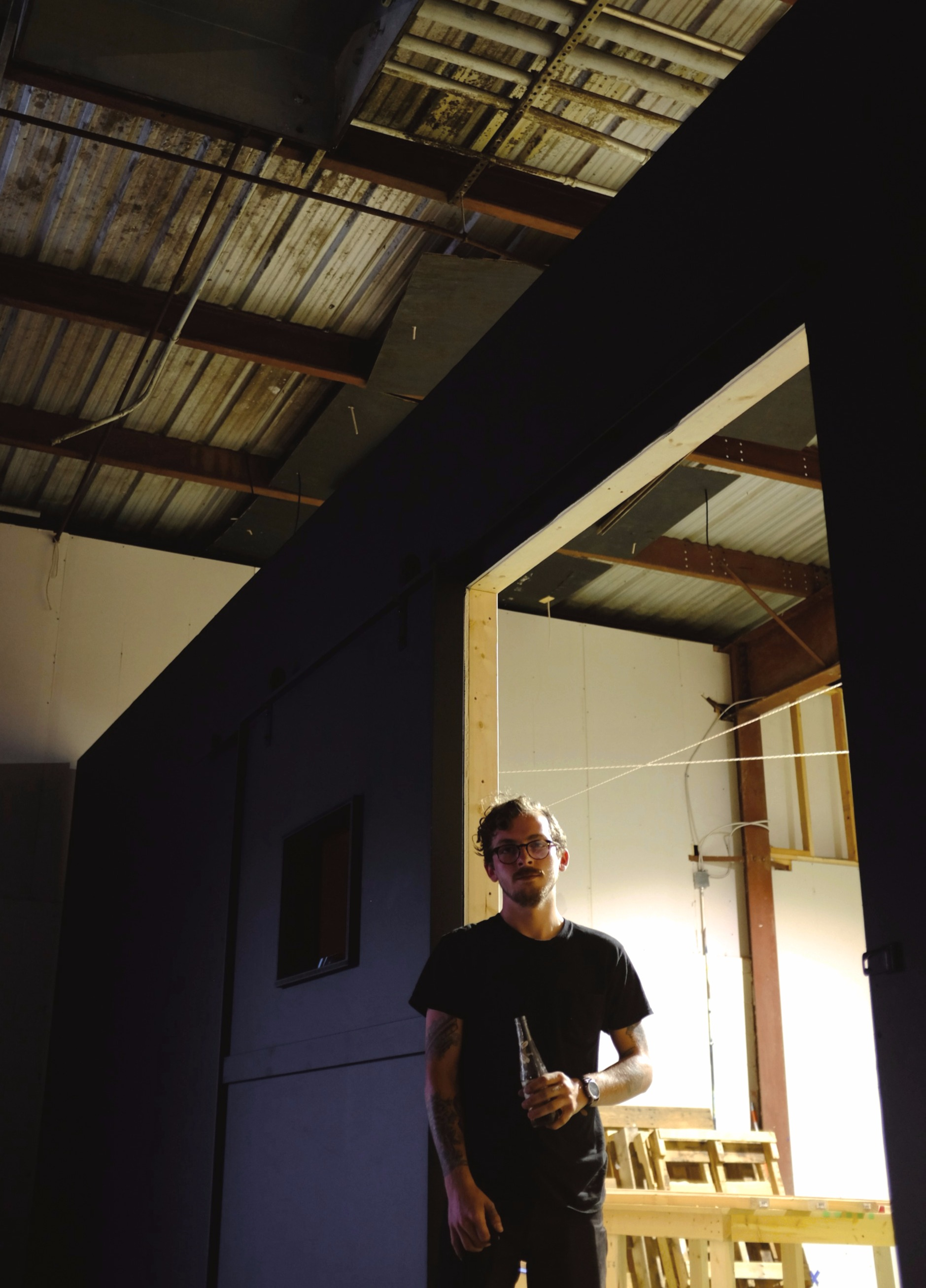 Mason Bovender, the designer and builder behind a creative company called Ninepound, stands at the entrance of his workshop space at The Bakery.