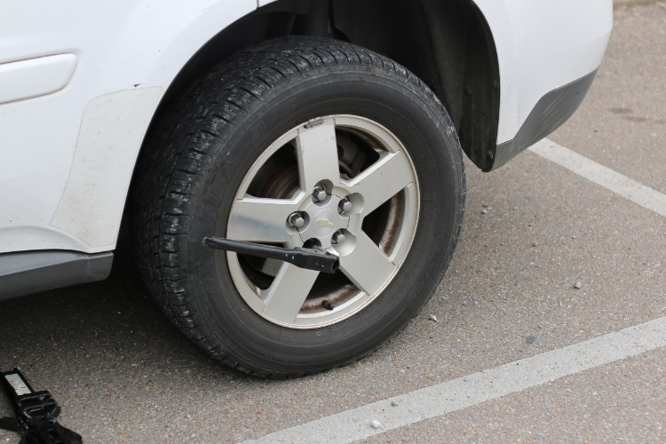 Use a tire iron to loosen the lug nuts before you lift the car. Photos by Braxton Maclean.