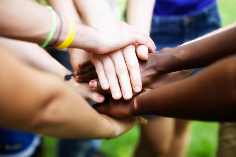 Closeup photo of group of hands stacked in a show of solidarity