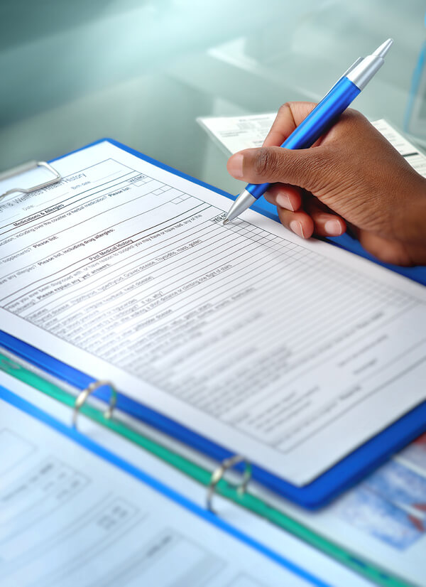 Young woman's hand holding a pen, filling out pre-screening questionnaire