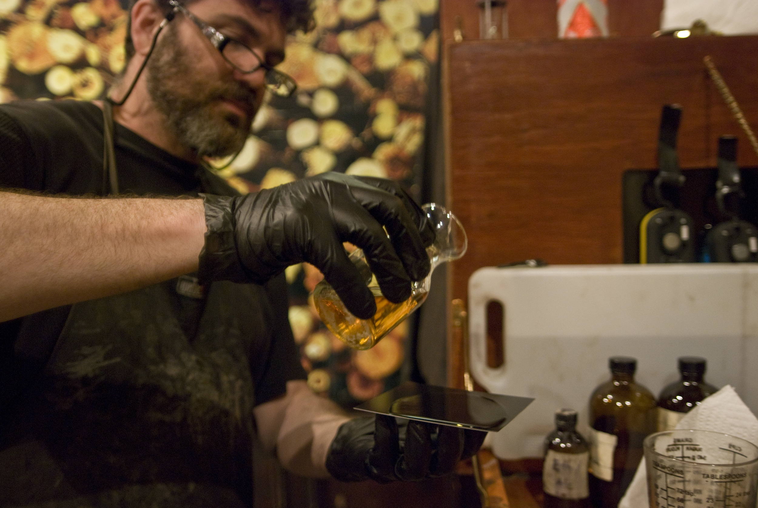 Scott pouring the syrupy Collodion onto a fresh metal plate- the first step in the tintype process