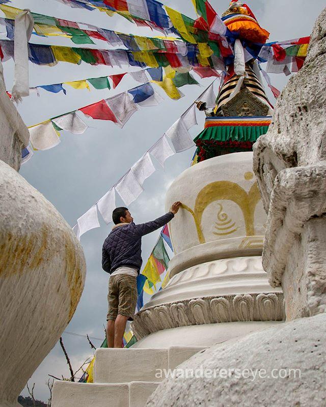 A man adds color to a freshly whitewashed stupa at the Thrangu Tashi Yangtse monastery in Namo Buddha, Nepal.