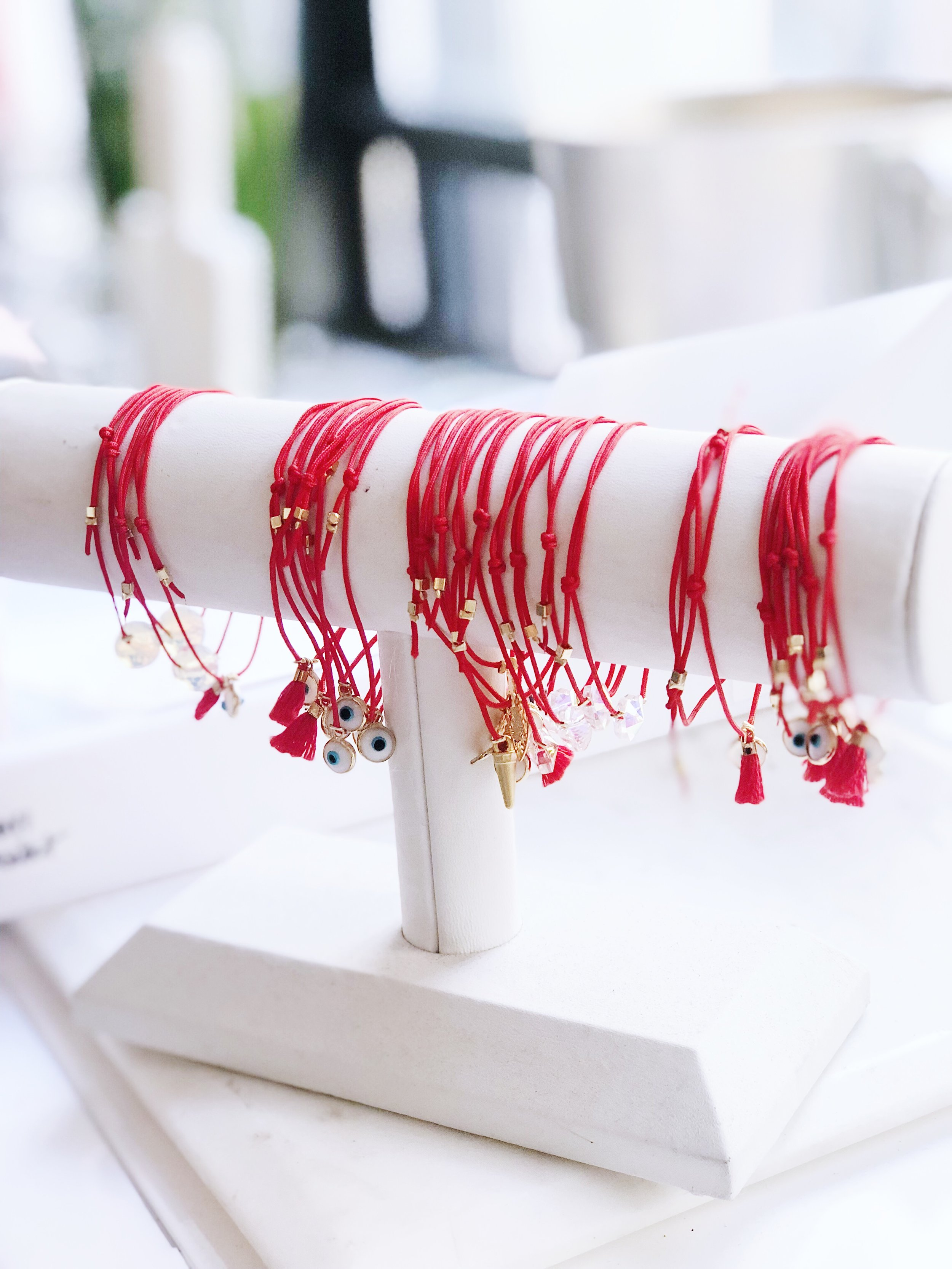 OUR RED STRING JEWELRY - ALL OF OUR RED STRING BRACELETS ARE HANDMADE BY US IN OUR NYC BASED STUDIO. EACH CHARM HAS BEEN HAND SELECTED AND ETHICALLY SOURCED. THEY'RE MADE TO BE WORN FOR PROTECTION AND GOOD LUCK. WE LIKE TO COLLECT THEM, STACK THEM AND NEVER TAKE THEM OFF. WE ALSO PROMOTE SHARING THEM FROM YOU WRIST TO SOMEONE WHO MIGHT NEED IT.WE SHOWER IN THEM, WORK OUT IN THEM, SWIM IN THEM AND NEVER TAKE THEM OFF, HOWEVER IF YOU WANT TO KEEP THEM LOOKING FRESH YOU MAY CONSIDER TAKING THEM OFF FOR CERTAIN ACTIVITIES.IF YOU EVER FIND YOURSELF IN NYC, WE INVITE YOU COME TO OUR STUDIO WHERE WE CAN CREATE A CUSTOM BRACELET FOR YOU.
