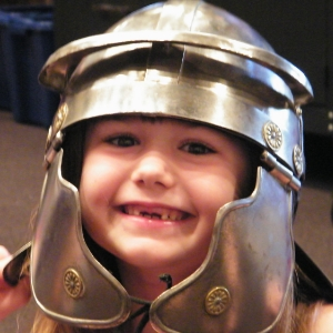 image of a child  smiling, wearing a silver knight's helmet