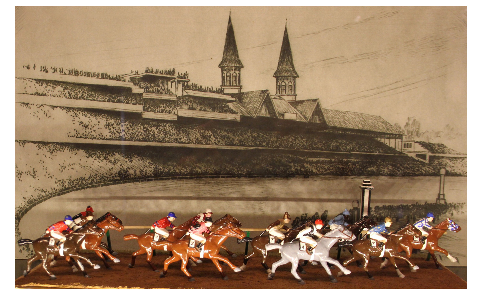 The Kentucky Derby diorama depicting the fastest 10 horses in Kentucky Derby history between 1930 and 1950, 11 horses featured as 2 horses ran the same time. Made by Barclay Manufacturing Co. of New Jersey. Painted in 1992 by Dr. William Schneider.