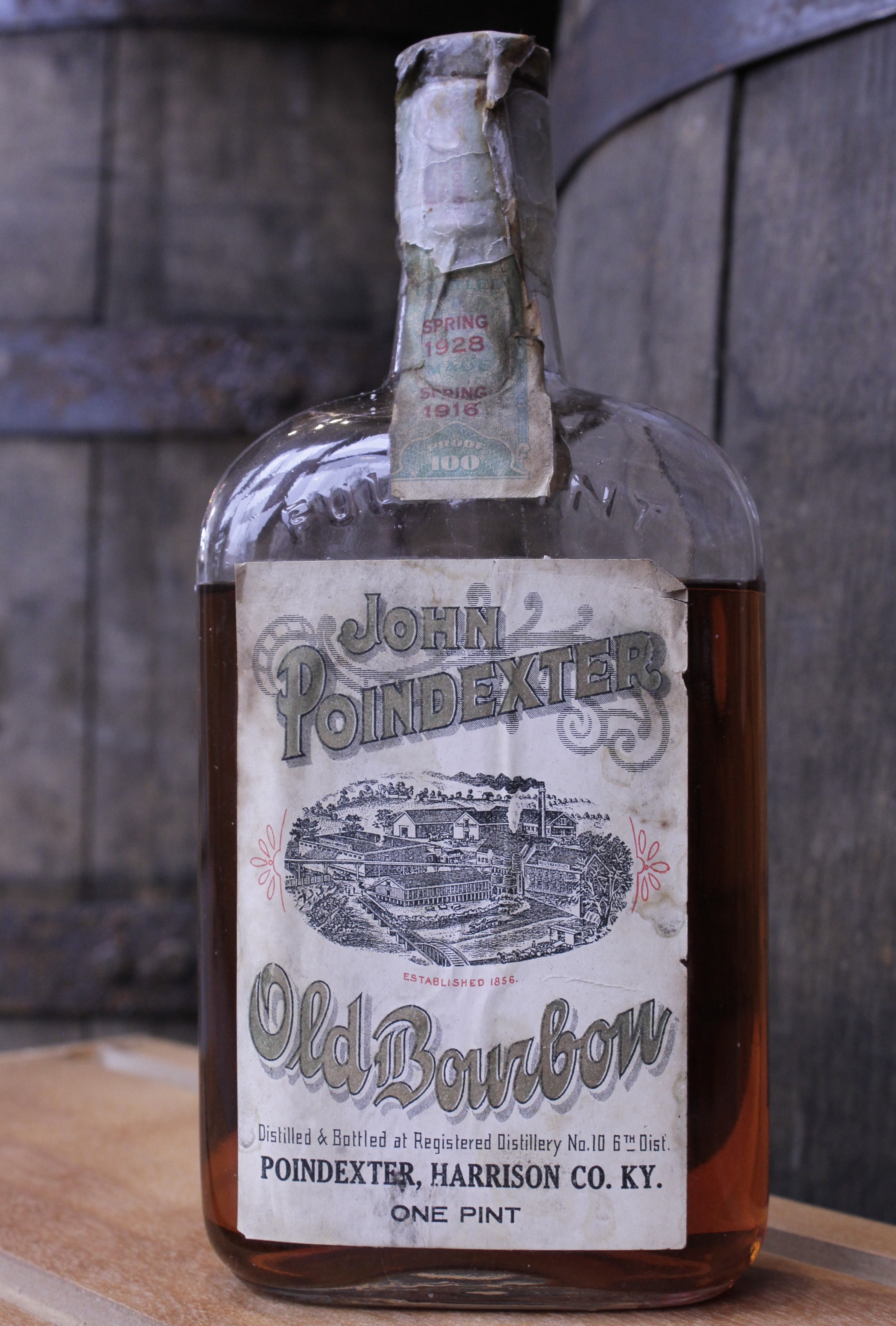 JOHN POINDEXTER OLD BOURBON    About the Product   One pint of Kentucky bourbon (100 proof), aged 12 years, bottled in bond. Distilled in spring 1916** by Wiglesworth Bros. Co. Bottled in spring 1928** by Joseph Wolf.  Introduced by John Poindexter in the 1850s and later acquired by the Wiglesworth Bros. Co., this brand of sour mash bourbon remained in production until Prohibition.   About the Distillery   6th Dist., RD #10, Wiglesworth Bros. Co. (1869 – 1919). Harrison County, Kentucky, USA.  Located on the South Fork of the Licking River four miles northwest of Cynthiana, this distillery was built in 1856 by John Poindexter. In 1869 the Wiglesworth family acquired it, tore it down and rebuilt it. By 1910 the mashing capacity had been increased to 300 bushels per day, and there were three bonded warehouses with a storage capacity for 20,000 barrels. In the late 1910s the officers were J. M. Wiglesworth, president and W. T. Wiglesworth, secretary-treasurer. Products included Old G. W. Taylor, Poindexter Bourbon, and Wiglesworth Bros. Sweet Mash. The distillery closed at Prohibition.  In 1924 all the whiskey in storage was transferred to the concentration warehouses of James E. Pepper & Co., a facility in Lexington that had been leased in 1907 for 20 years by Joseph Wolf of Chicago, where it was bottled for medicinal spirits.