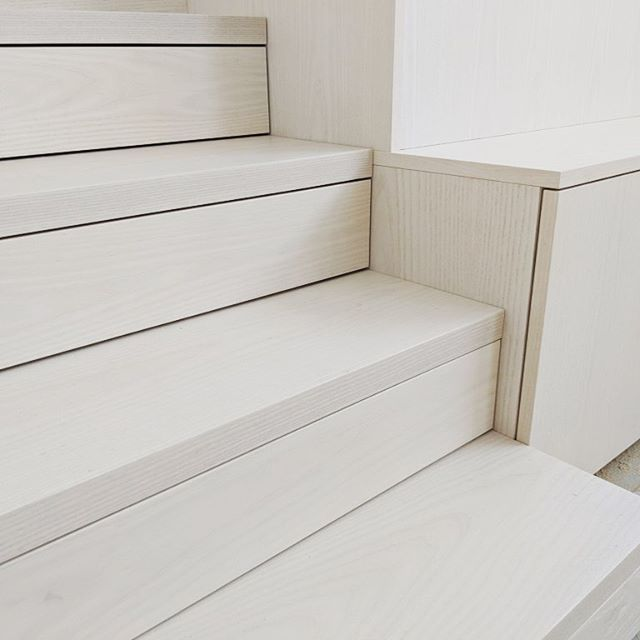 Detail of our bleached solid white ash staircase with touch open drawers transitioning nicely into the media center on a project by @michelleleejin @regenerationdesignstudio