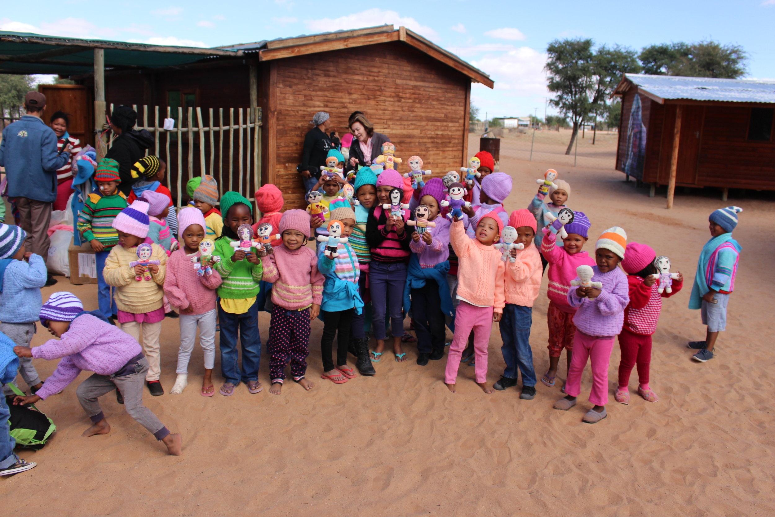 """Happy Monday!!  Don't have to say much......Just take a moment to  see their smiles!   We are very grateful to collaborate with  Sesego Cares in South Africa. This was a part of our """"BIG"""" campaign and we managed to send 50 dolls to children who live in the desert.  Here is a quote from Sesego Cares:    This unique community is the oldest in the world, also one of the most special communities and people in our beautiful country. I thought it fitting for these members to receive the dolls. They stay in the desert.  Once again thanks for the amazing support. This was just brilliant and inspirational!"""