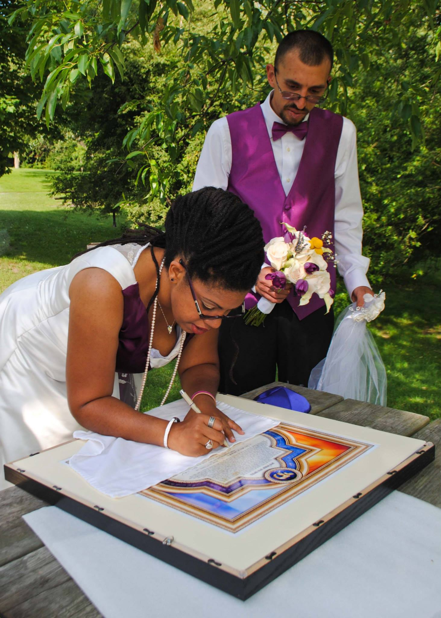 Couple signing Jewish marriage document at wedding