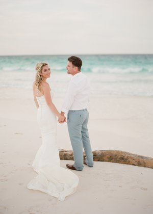 fine+art+photo+of+bride+and+groom+on+pink+sands+beach+near+driftwood.jpg