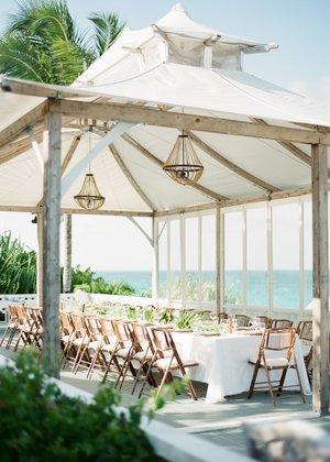 fine+art+photo+of+wedding+reception+table+under+white+canopy+on+deck+near+the+beach.jpg