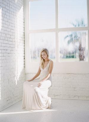 fine+art+photo+of+blonde+woman+in+white+dress+in+all+white+window+lit+room.jpg