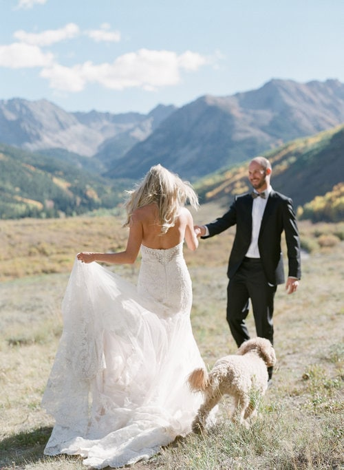 fine+art+photo+of+bride+and+groom+running+through+field+in+the+mountains+with+dog.jpg