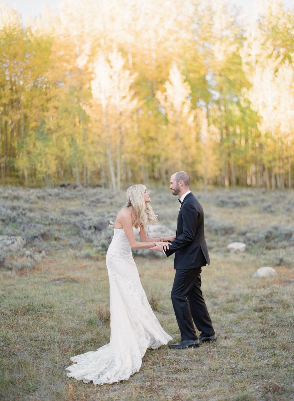 fine+art+photo+of+bride+and+groom+playfully+holding+hands+in+aspen+grove.jpg