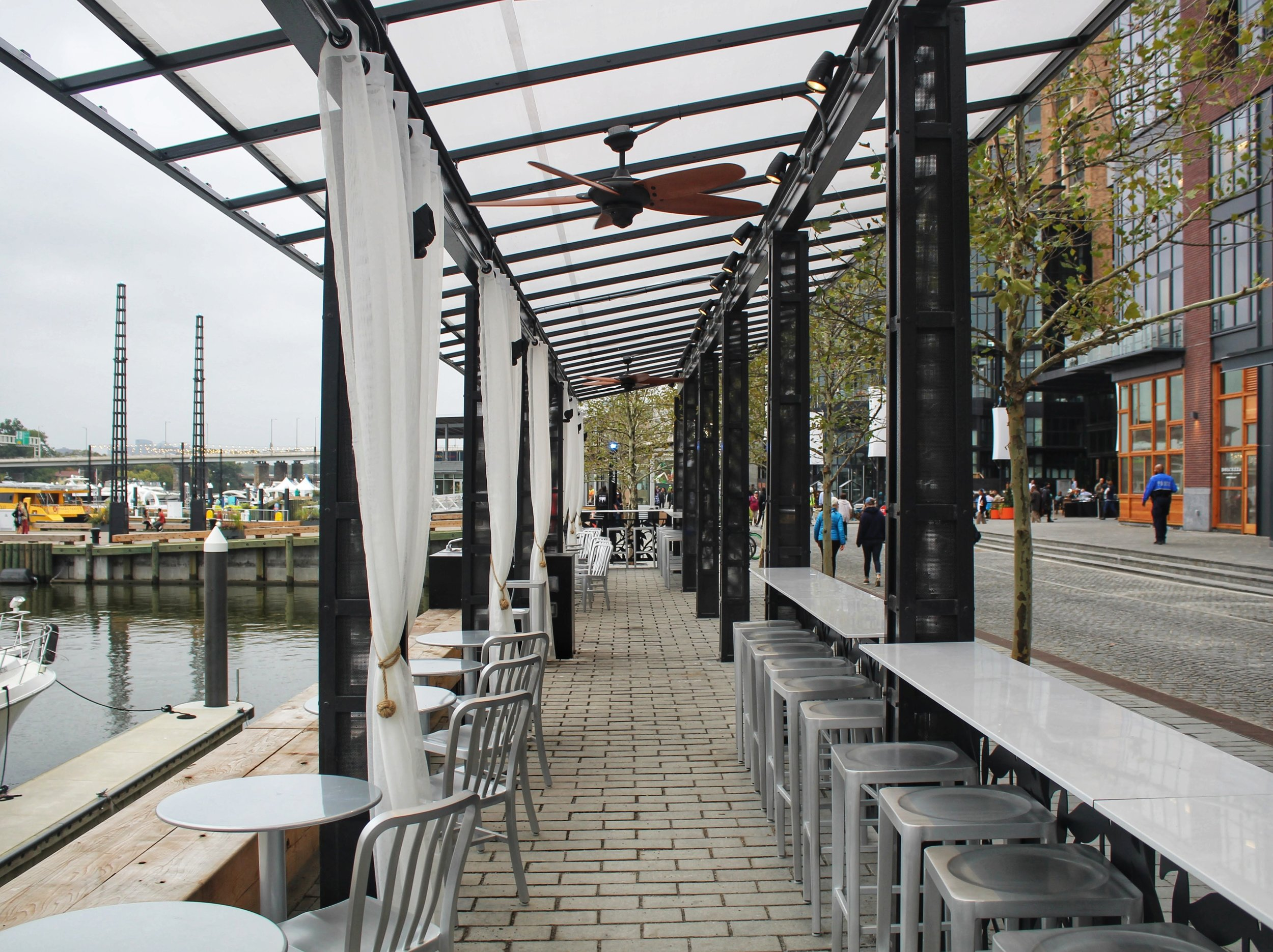 Seating for diners located between the pedestrian walkway and Washington Channel.