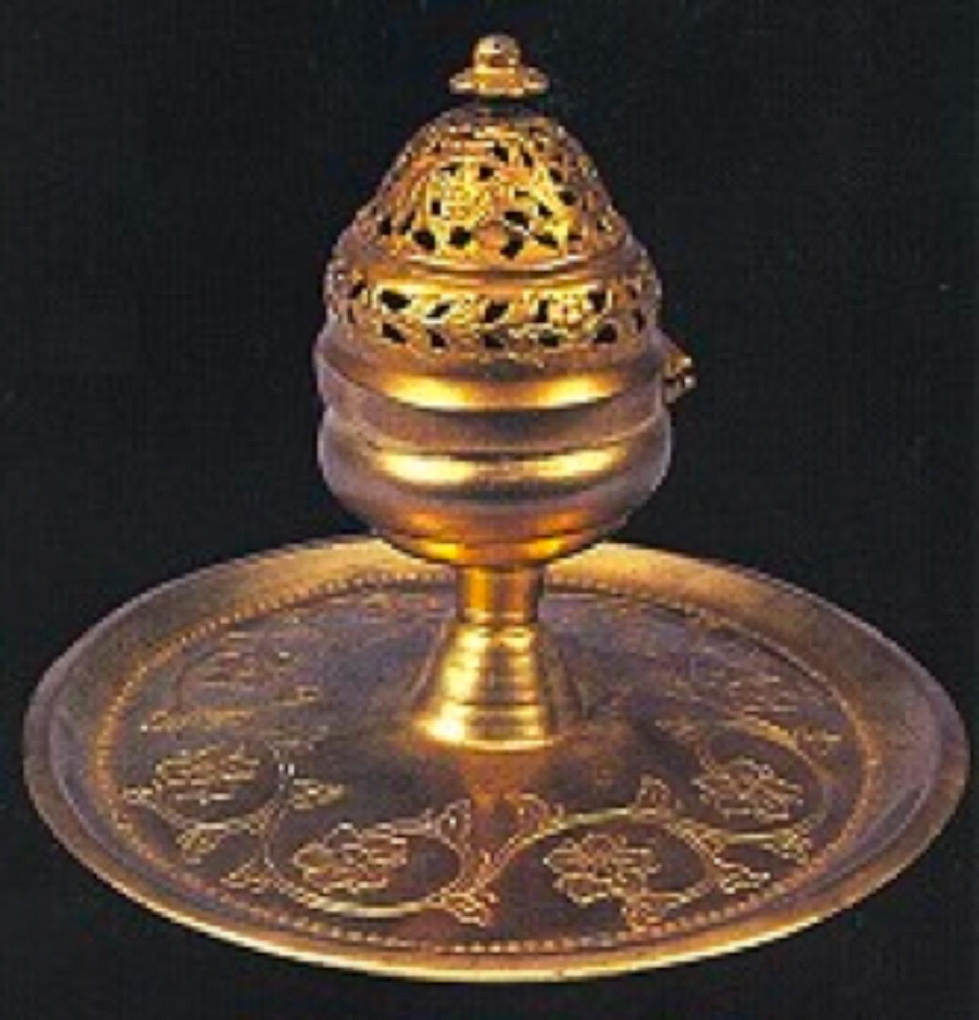 TOMBAK BUHURDAN Tabla çapı 19.5 cm ve yüksekliği 15 cm olan tombak buhurdan 19.yüzyıl ürünüdür. Küçük bir tepsiyi andıran tabla zemini iri kıvrımlı dallara bağlı rozet ve hatayilerden oluşan kalemişi bir çelenkle bezelidir. Desenlerin içleri, kumlanarak çökertilmiştir. Tablanın ağız kenarına yakın kısmı, baskı tekniğinde yapılmış bir boncuk dizisiyle çevrilidir. Dışa dönük kenarlı tablanın merkezindeki bir bombeden yükselen gövde, dövülerek şekillendirilmiştir. Ateşlik kısmı bezemesiz olup ağız kenarına doğru daralmaktadır. Ateşliğe menteşeli ve ona geçme kapak, boğumlu bir kubbe şeklindedir. Düz olan ağız kenarının üstündeki boğum, rozet ve yaprak bağlantılarından oluşturulmuş bir çelenkle bezelidir. Yaprak ve rozet araları oyulmuştur. Tepe boğumunda birbiri içine geçen, araları oyulmuş, girift kıvrık dallar, yaprak ve çiçekler bulunmaktadır. Ve tepesinde papatya biçiminde bir tutamak yer almaktadır.