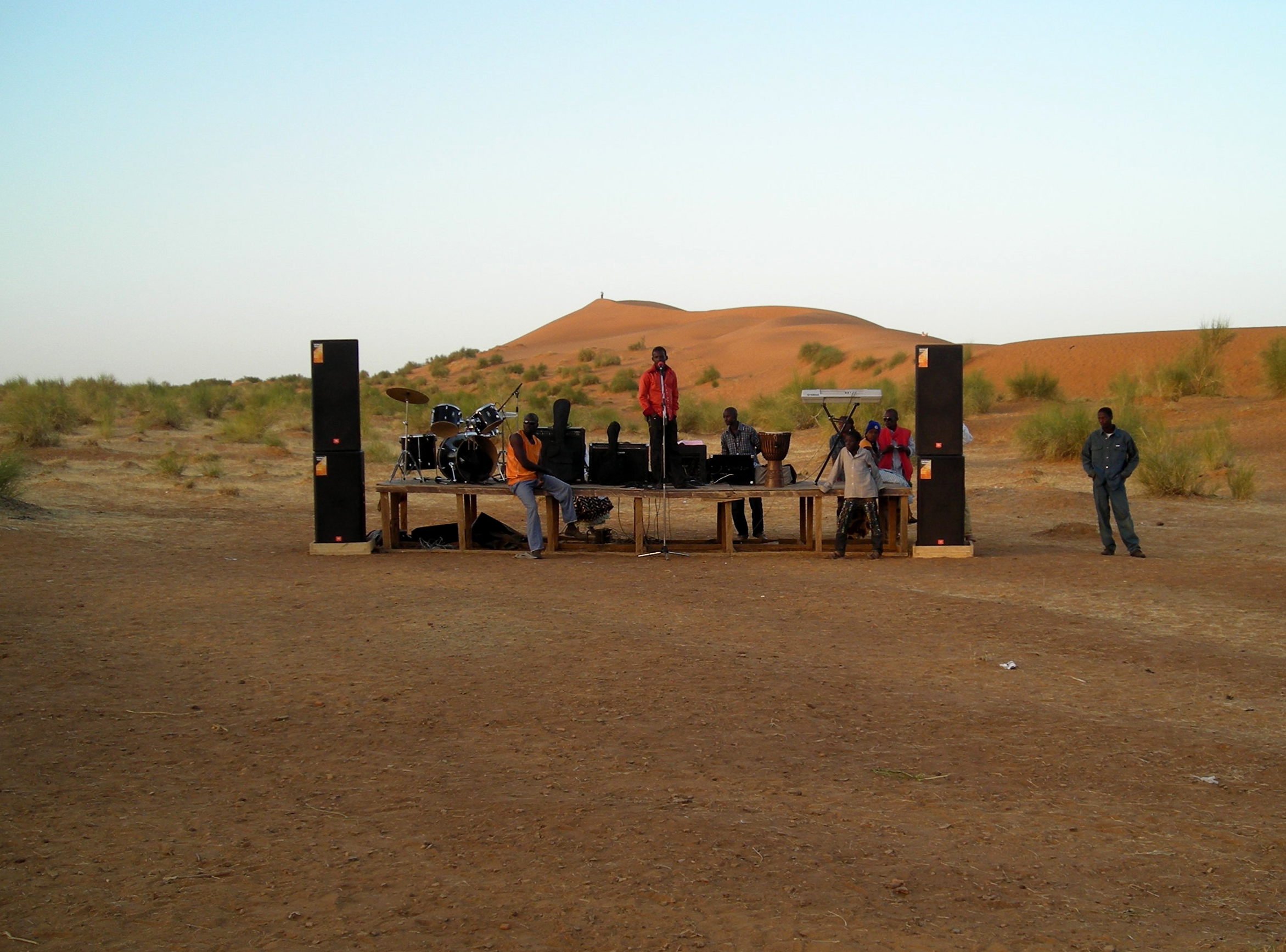 Nasser Maïga making a first soundcheck at the Sweden/Mali voices festival in Koïma, jan 2010. The red dunesof Koïma in the background.