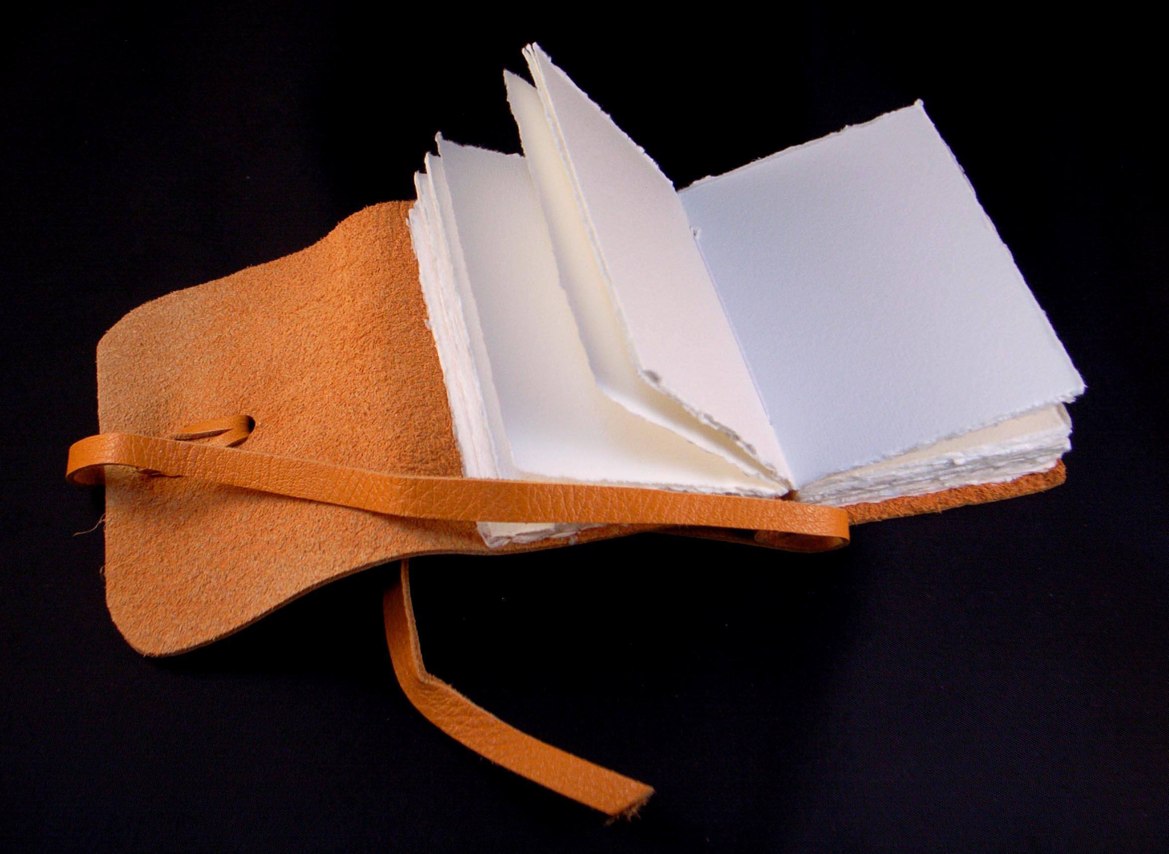 taccuino con copertina in pelle di artigianato fiorentino. realizzato a mano con carte artigianali