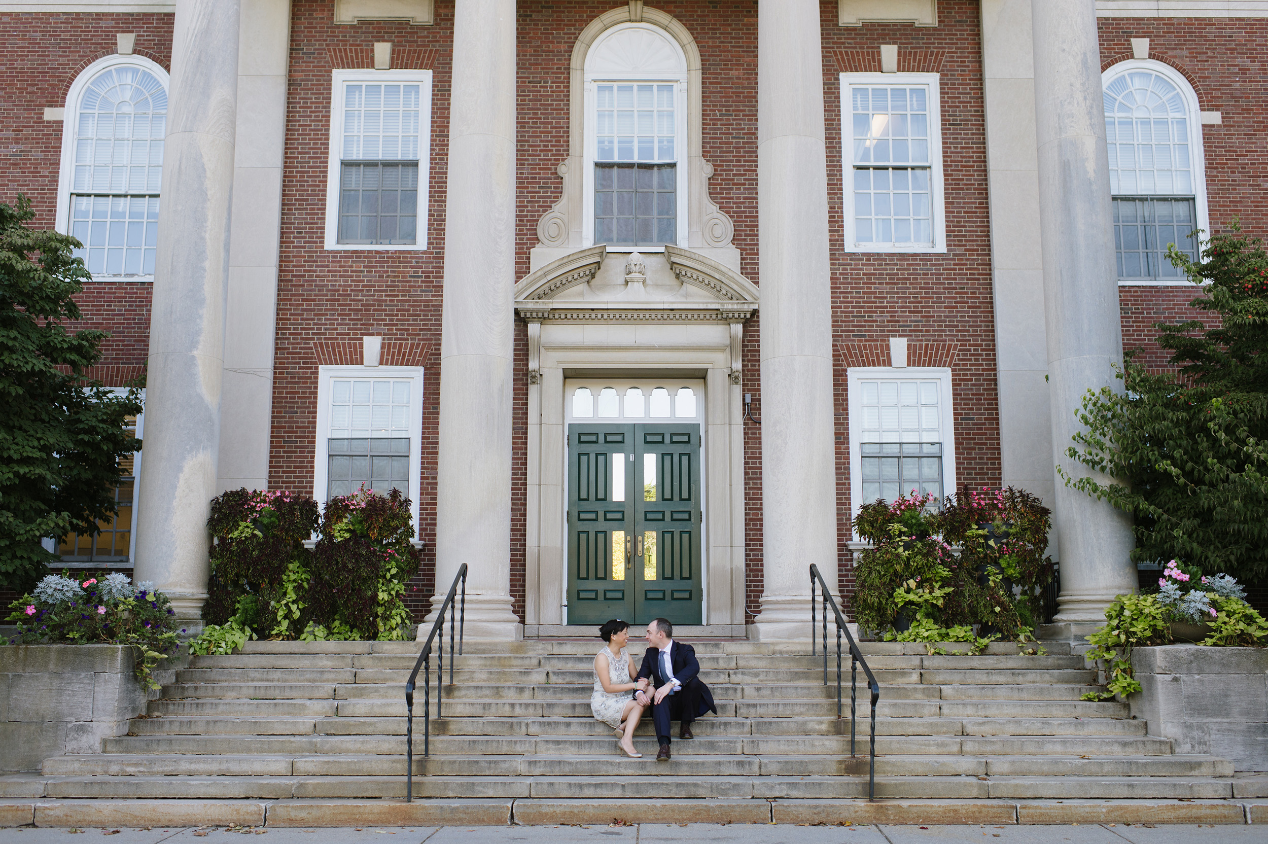 Bride and groom sitting on the steps of Newton Town Hall on their wedding day