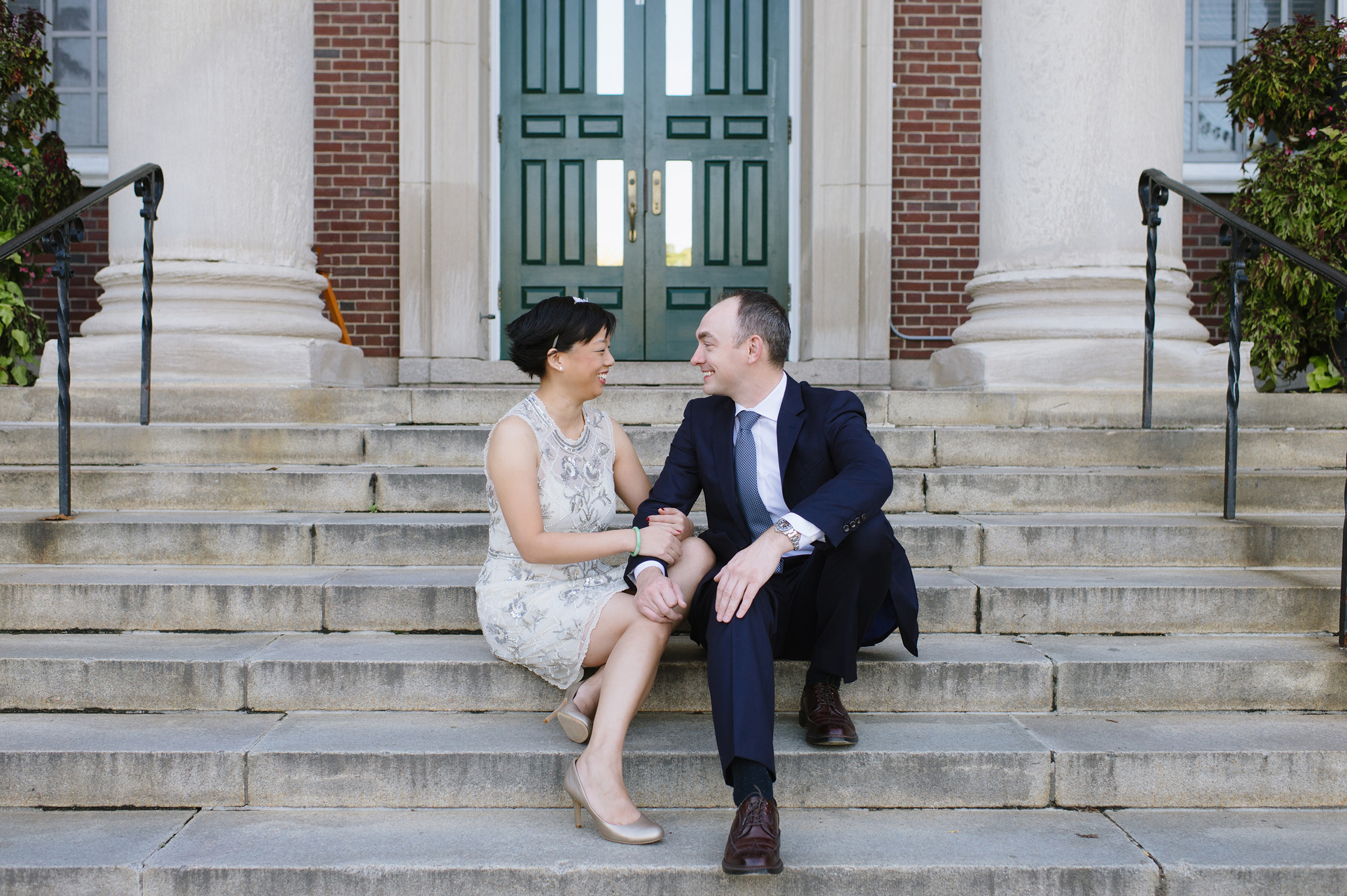 Bride and groom sitting on steps of Newton Town Hall