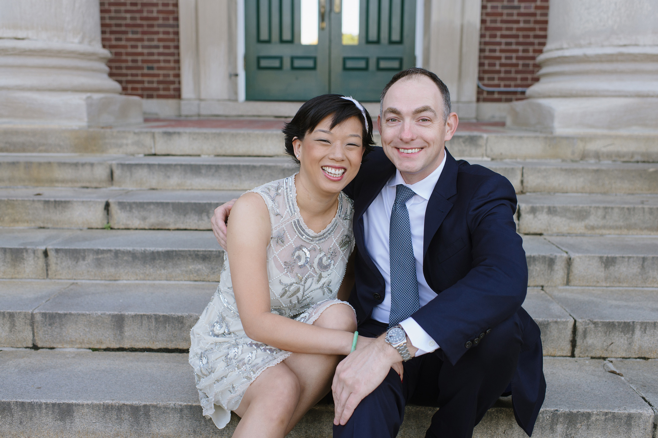 Bride and groom smiling while sitting on steps of Newton Town Hall on their wedding day