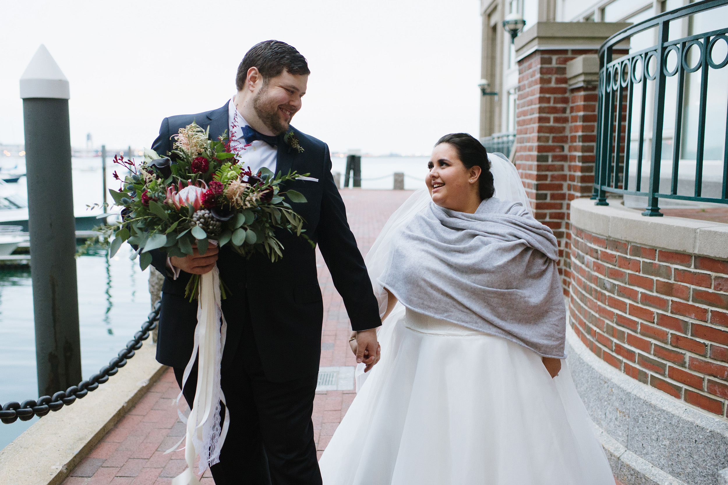Couple walking and smiling at the Boston Waterfront on their wedding day.