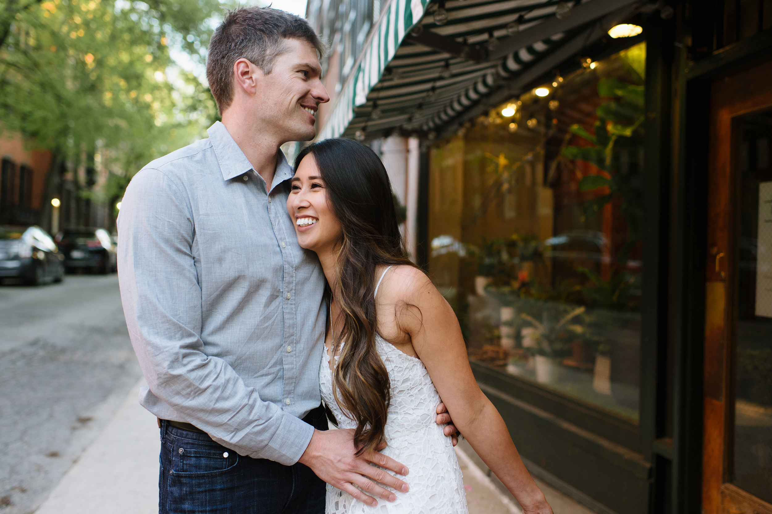 Couple standing out in front of flower shop smiling in Beacon Hill