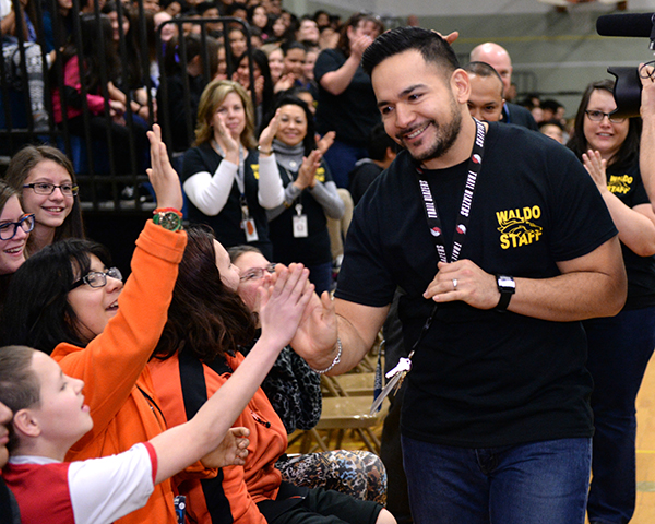 Ricardo Larios gets high fives and cheers from excited students as he makes his way to the front of the gymnasium to accept his surprise Milken Educator Award.  Photo Courtesy of the Milken Family Foundation.