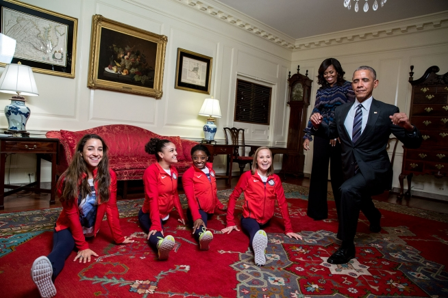 President Barack Obama attempts his best split with the gold medal 2016 U.S. Olympic Women's Gymnastics Team with First Lady Michelle Obama watching in the Map Room, prior to an event to welcome the 2016 U.S. Olympic and Paralympic teams to the White House to honor their participation and success in the 2016 Olympic games in Rio de Janeiro, Brazil, Sept. 29, 2016.