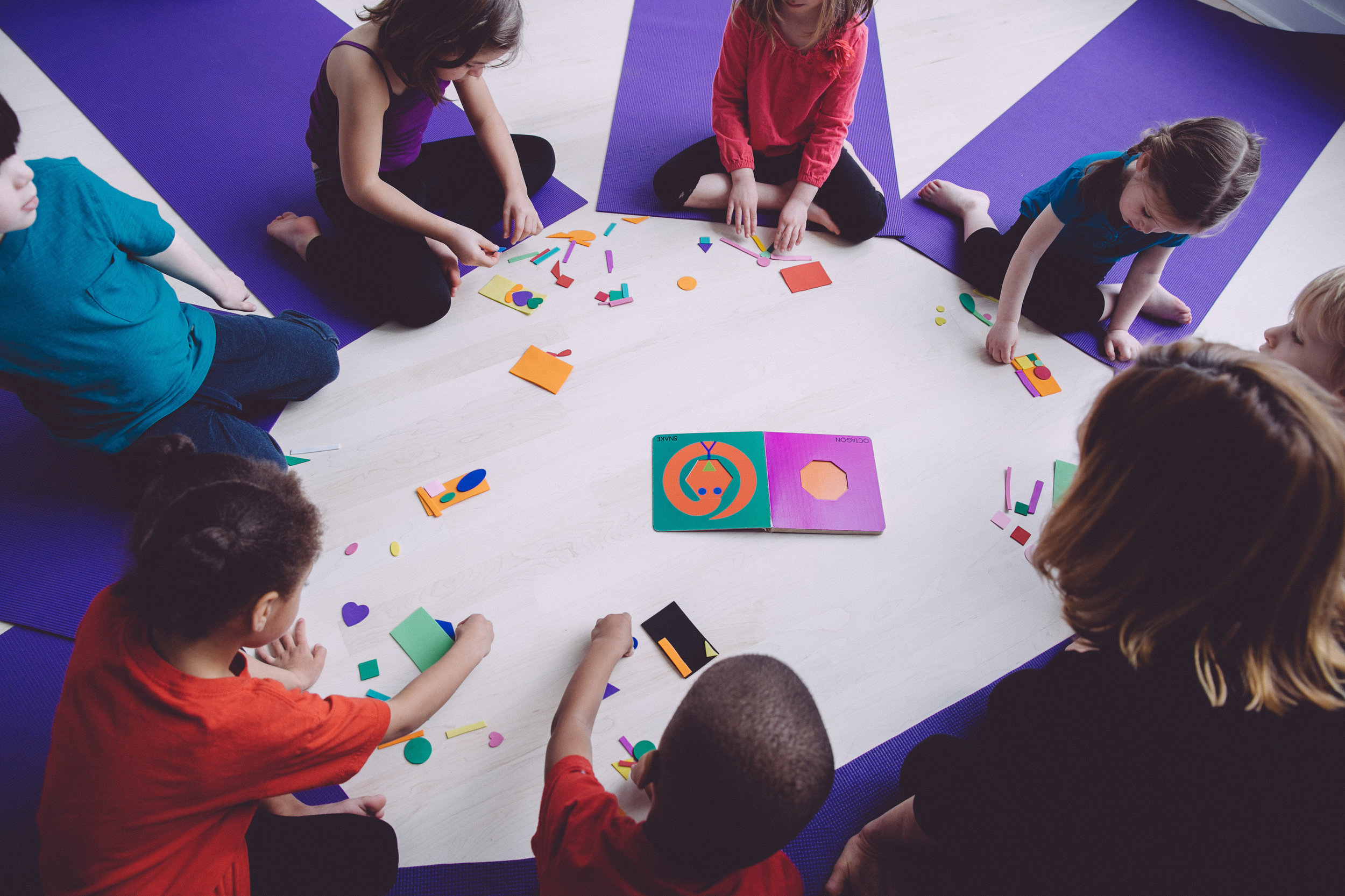 "Pre-school children enjoying a geometric visual art project inspired by Lois Ehlert's book ""Color Zoo"""