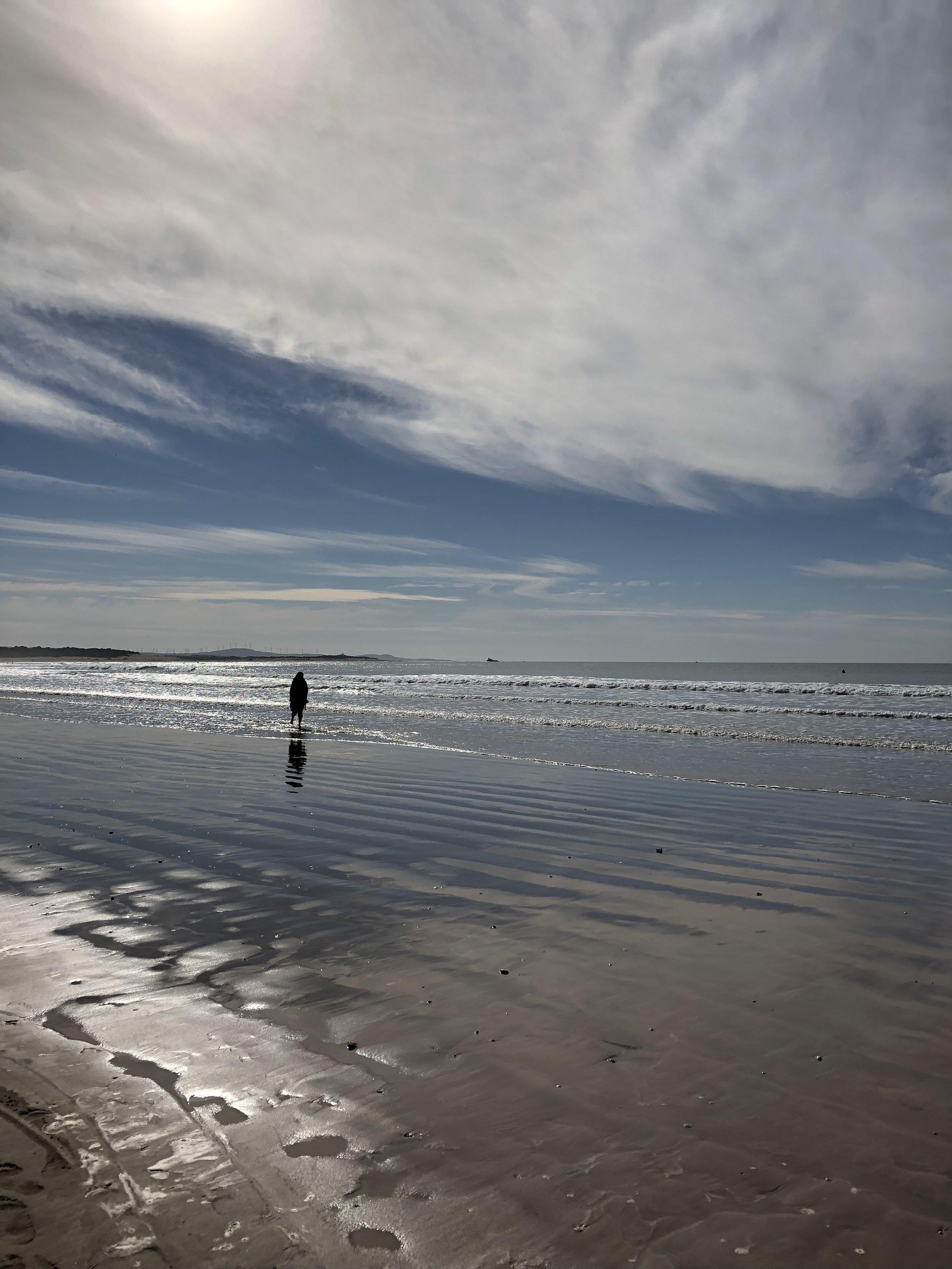 裸足になり海辺を歩くモロッコ人の女性。