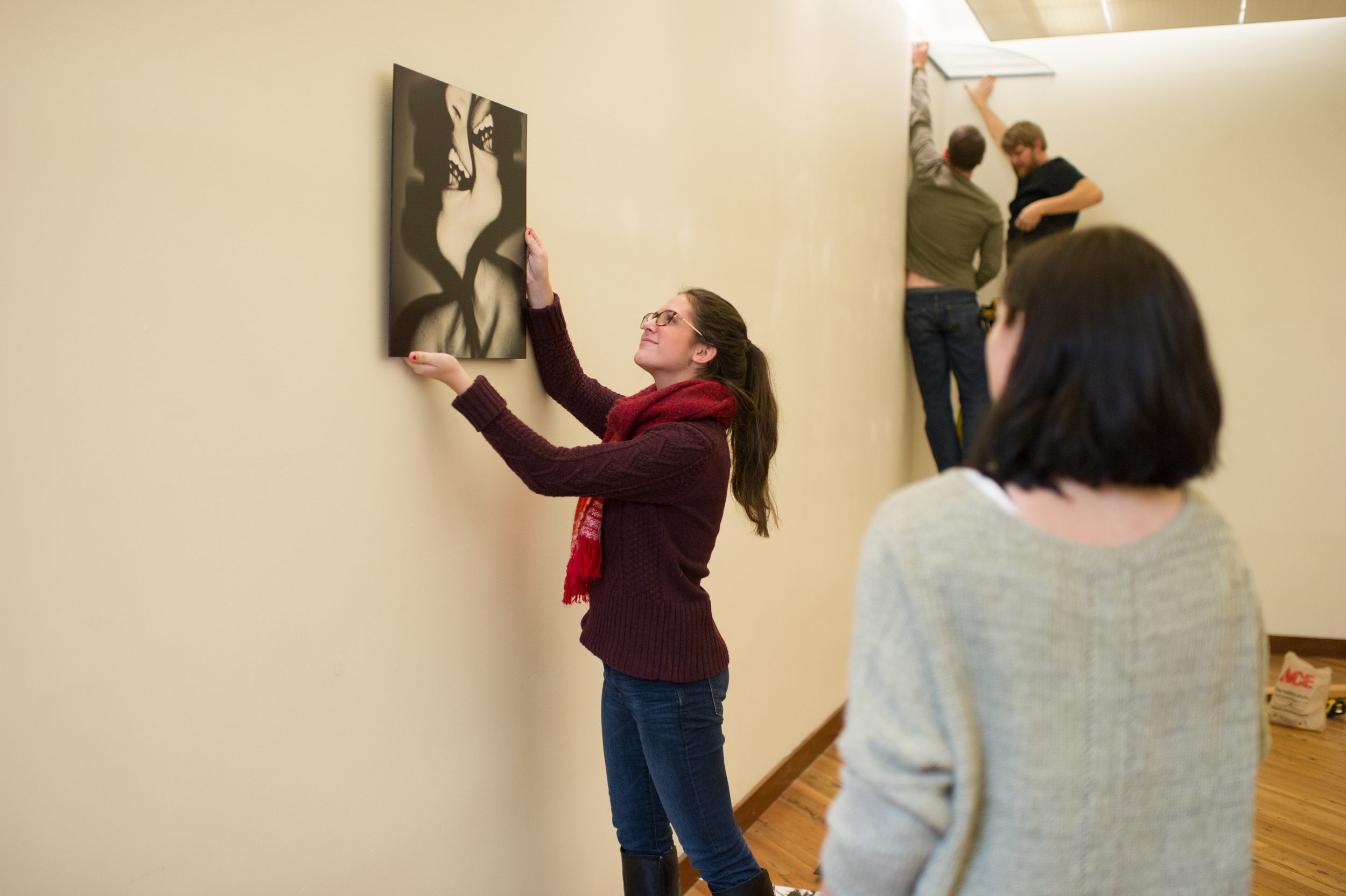 Students in The Future Is Now work to install their exhibition in the Green Building Gallery
