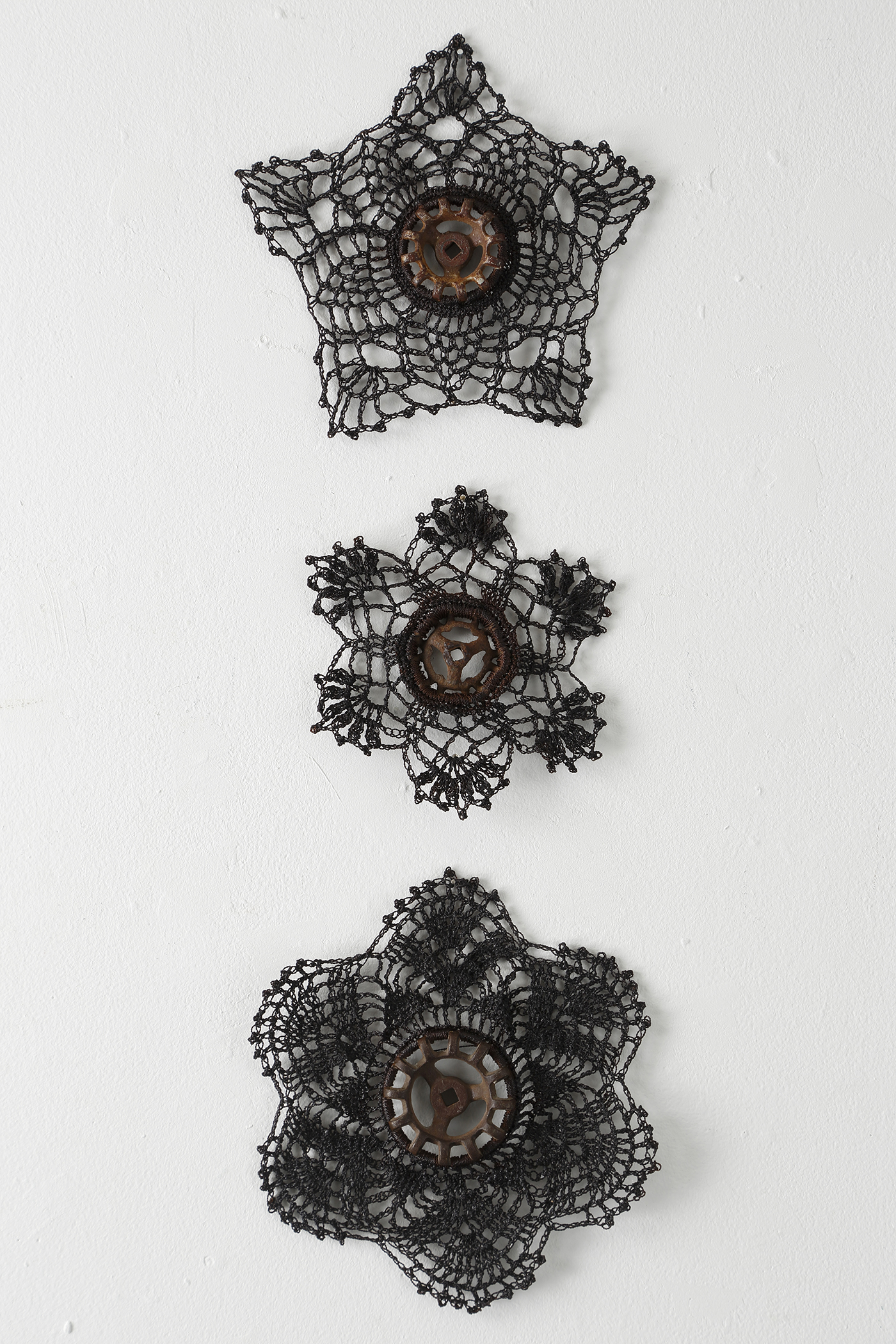 """A Trinity of Faucets"" by Bette Levy, Hand crochet, nylon cord, faucets, various sizes, 2018"